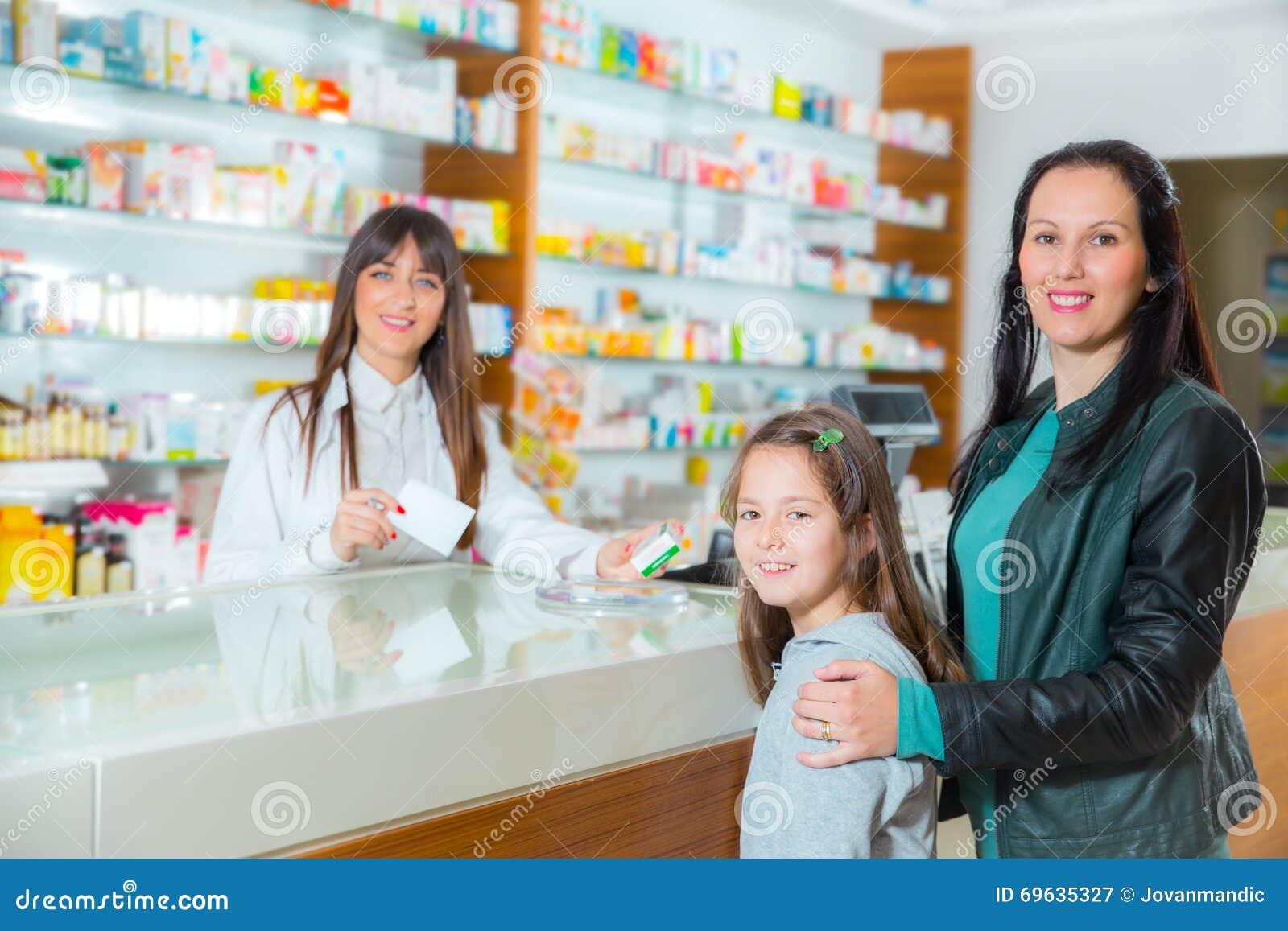 Ppharmacist που δίνει τις βιταμίνες στο κορίτσι παιδιών στο φαρμακείο φαρμακείων