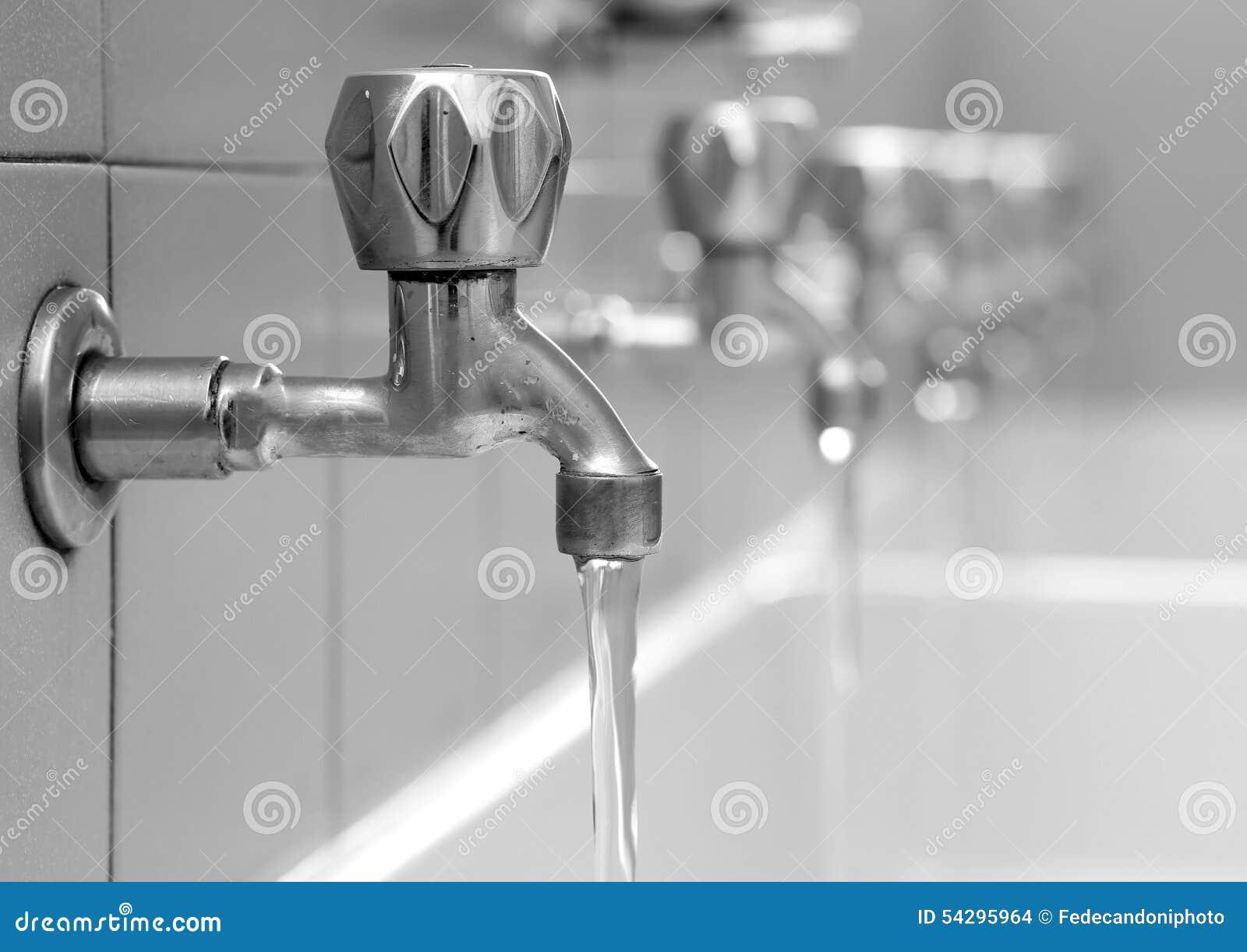 Öppna vattenkranar med vatten som flödar i de ändrande rummen för ...