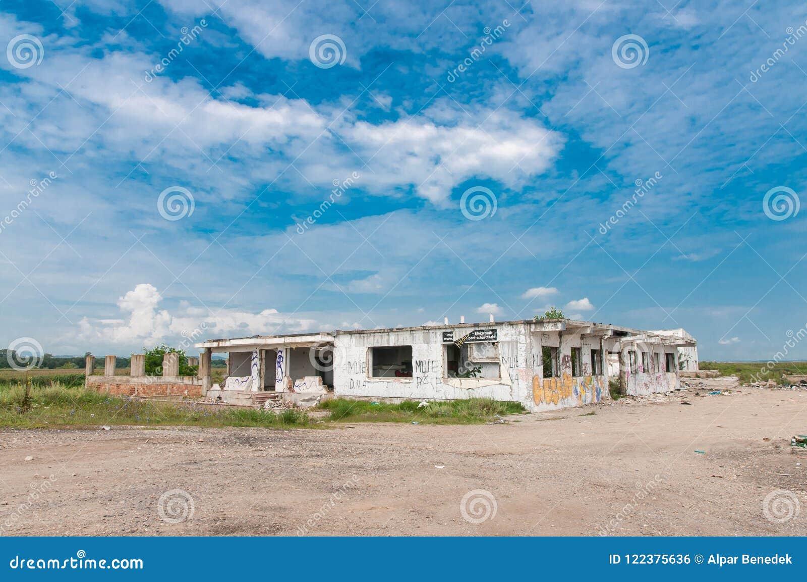 Prédio de escritórios abandonado com o céu azul bonito, anti slogan do governo nas paredes