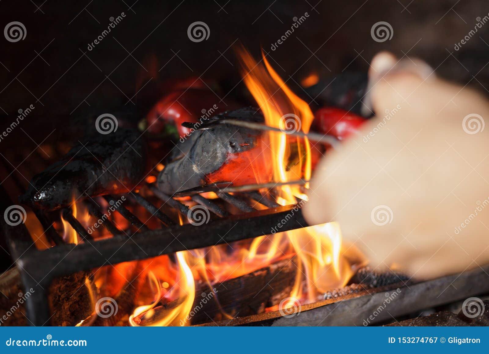 Préparant la délicatesse Ajvar du Balkan traditionnel, grillant le paprika sur une flamme nue