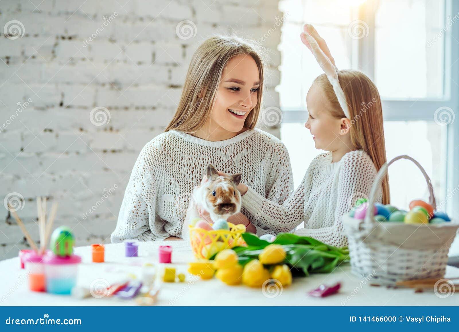 Préparation à Pâques avec ma mère La petite fille avec sa course de mère un lapin décoratif à la maison