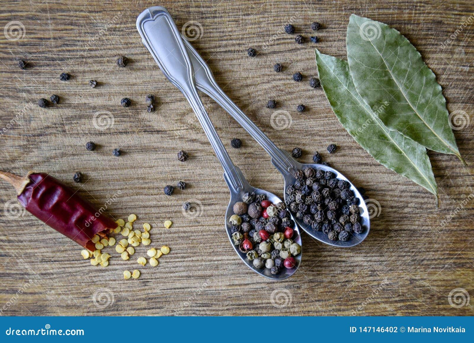 Préparation et grains de poivre d épice en cuillères en métal, une cosse cassée de poivron rouge chaud avec des graines et feuill