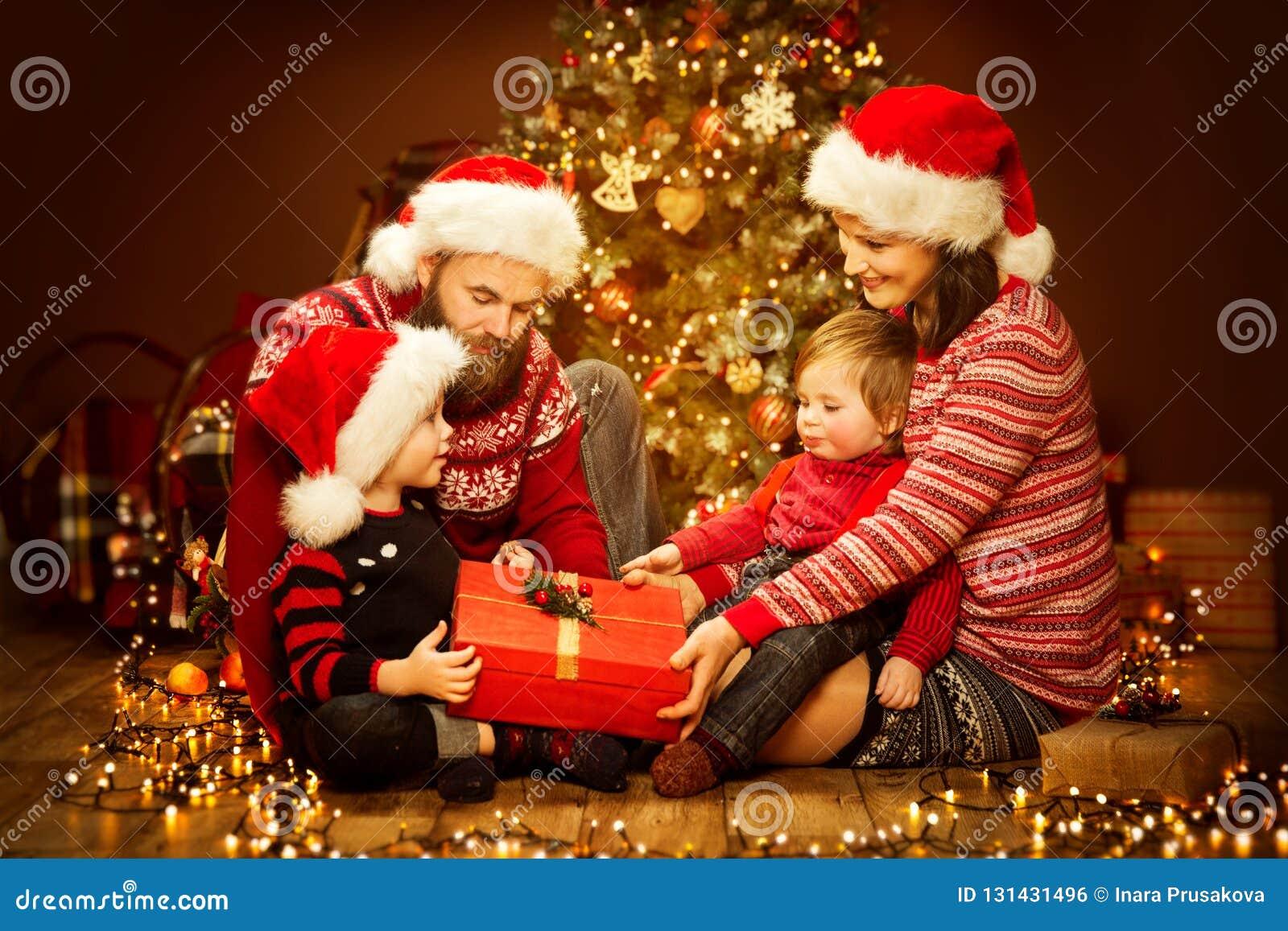 Présent d ouverture de famille de Noël, arbre et cadeaux de Noël, père heureux Mother Child et bébé dans Red Hat