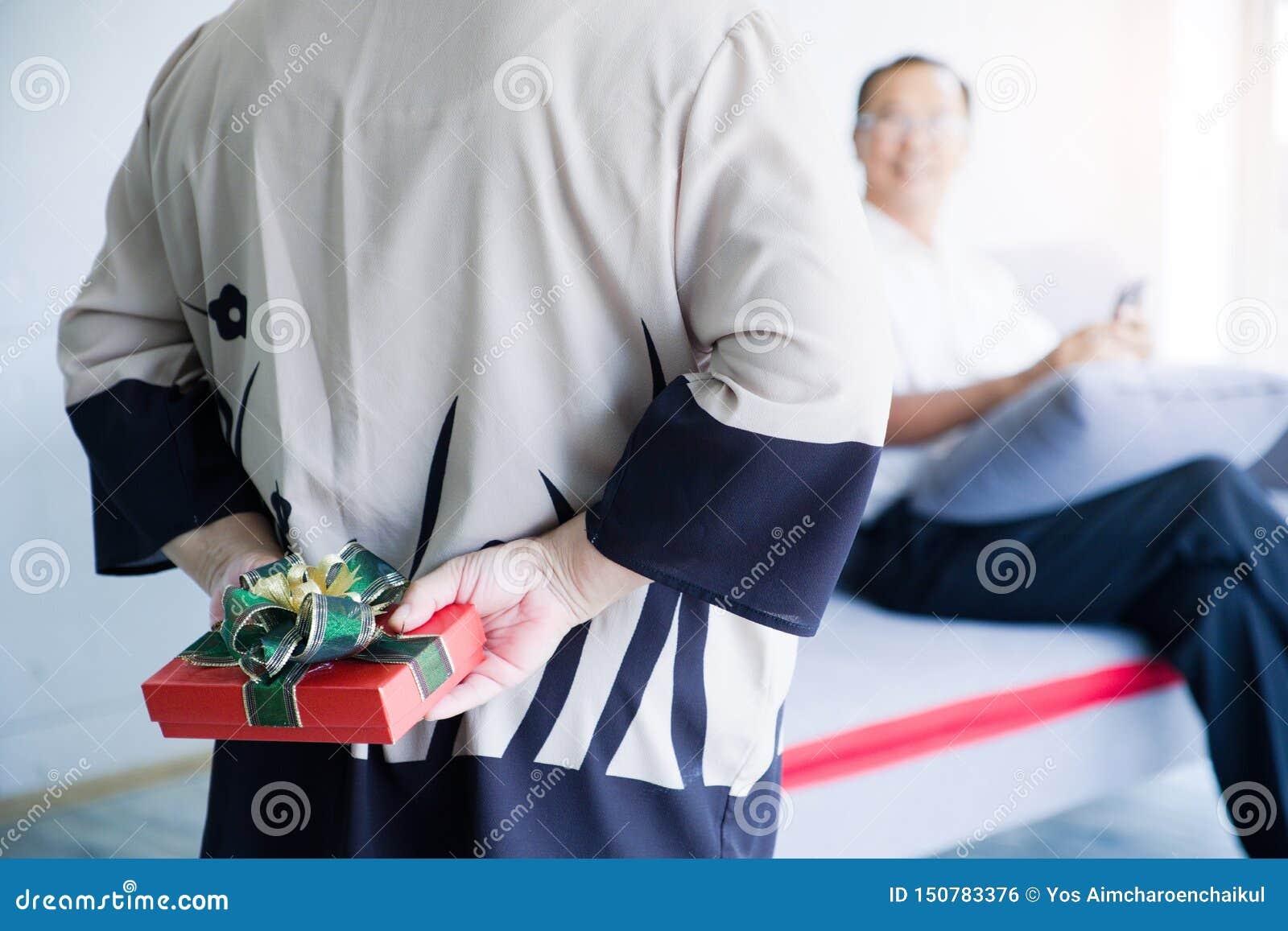 Présent de dissimulation de femme supérieure pour son mari derrière le dos sur valentineday Célébration supérieure de l Asie de c