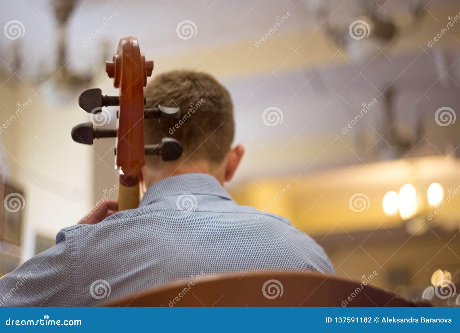 Próximo acima de um homem que joga o violoncelo, um concerto real, vista traseira