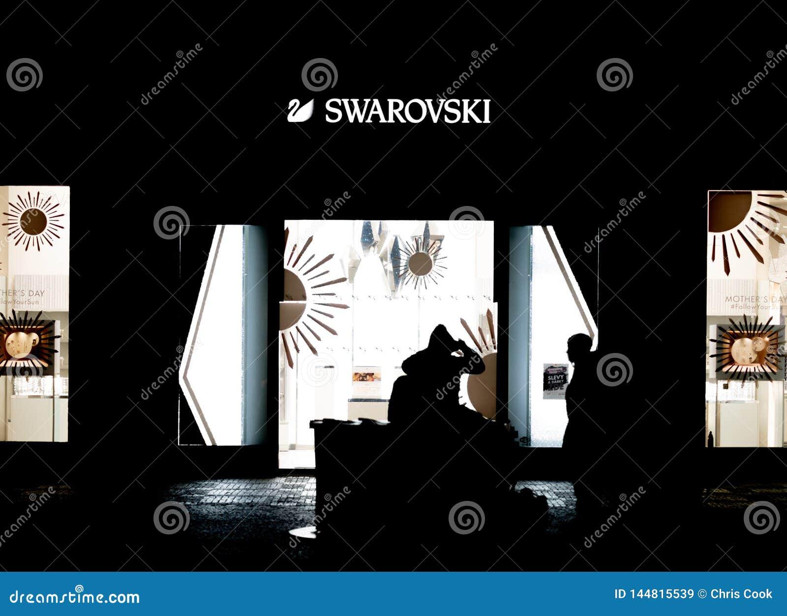 PRAAG, CZECHIA - 10TH APRIL 2019: Een paar zit voor een Swarovski-winkel laat bij nacht in Praag