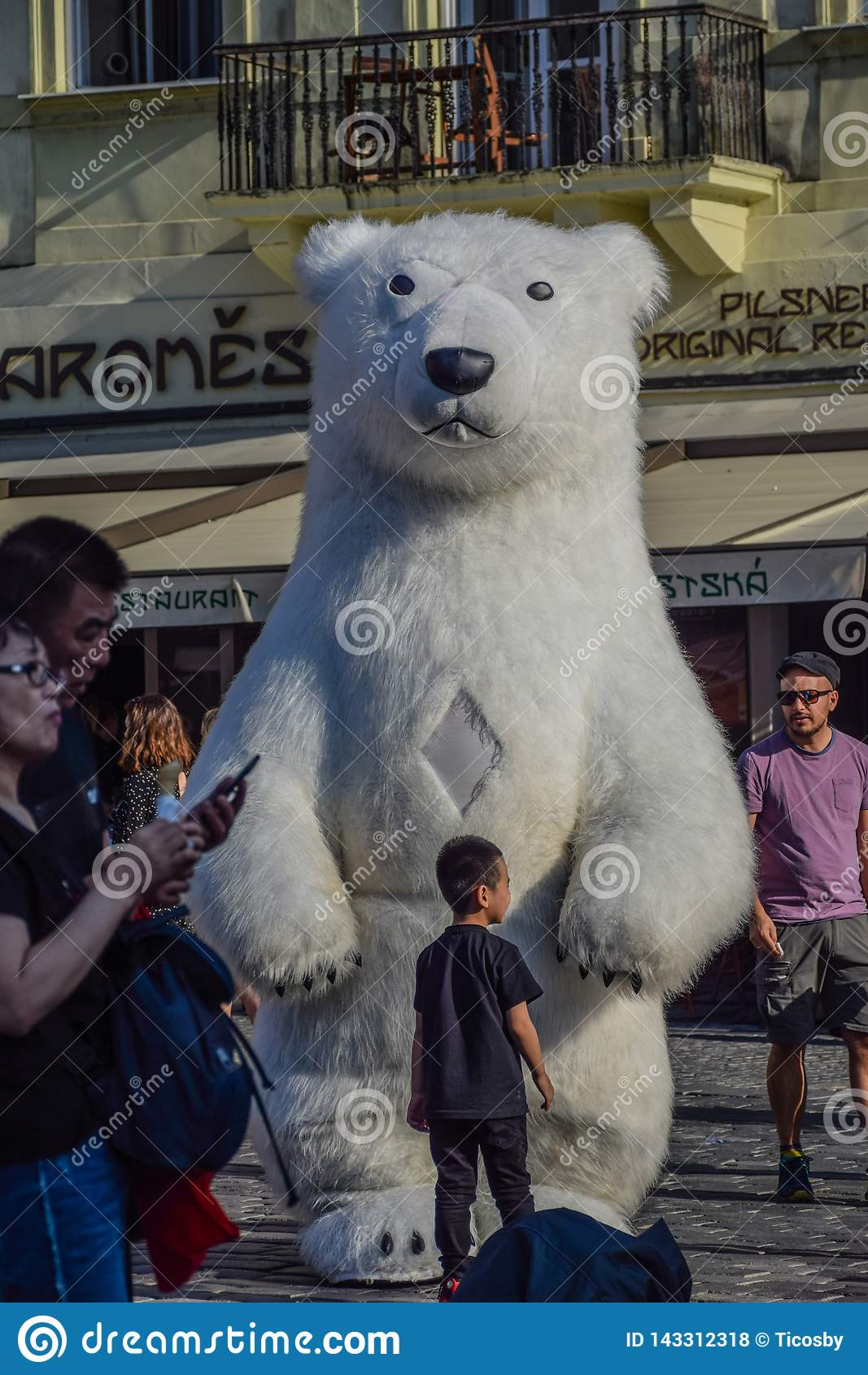 Praag, Tsjechische Republiek - 17 September, 2019: De grappige jonge geitjes spelen met een reuze opblaasbare ijsbeer in de Oude