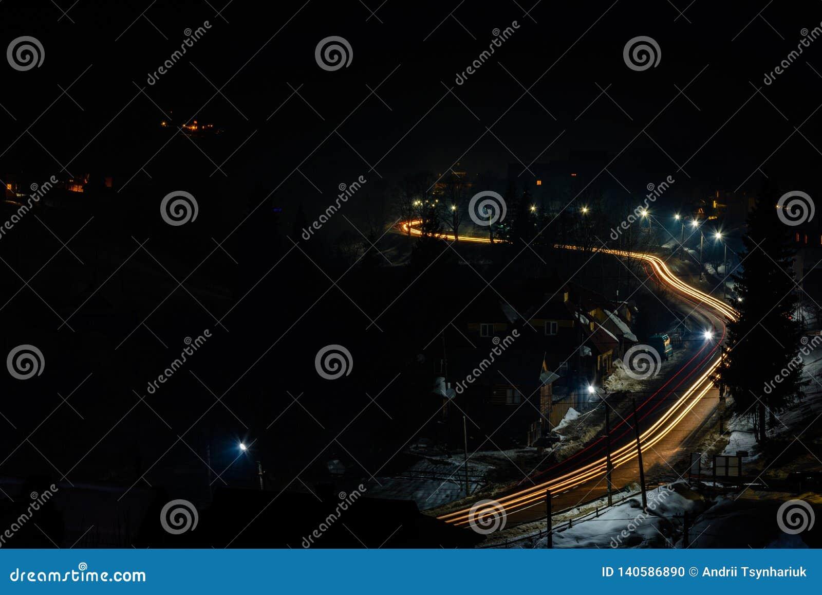 Prachtig nachtlandschap van het Oekraïense dorp in heldere lichte en vage automobiele lichten