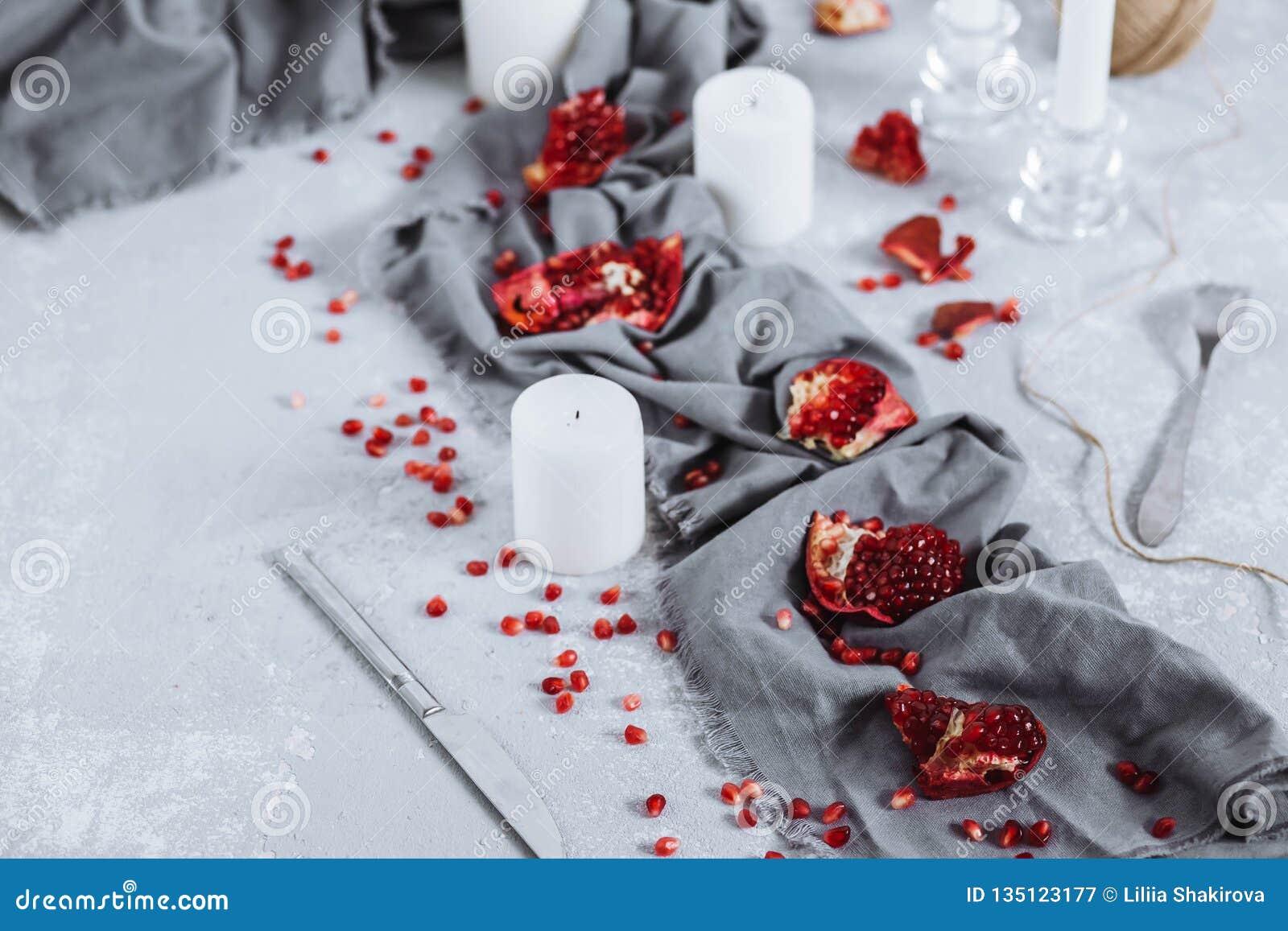 Prachtig verfraaide lijst met stukken rode granaatappel, handdoeken en kaarsen Voedselfoto met fruit