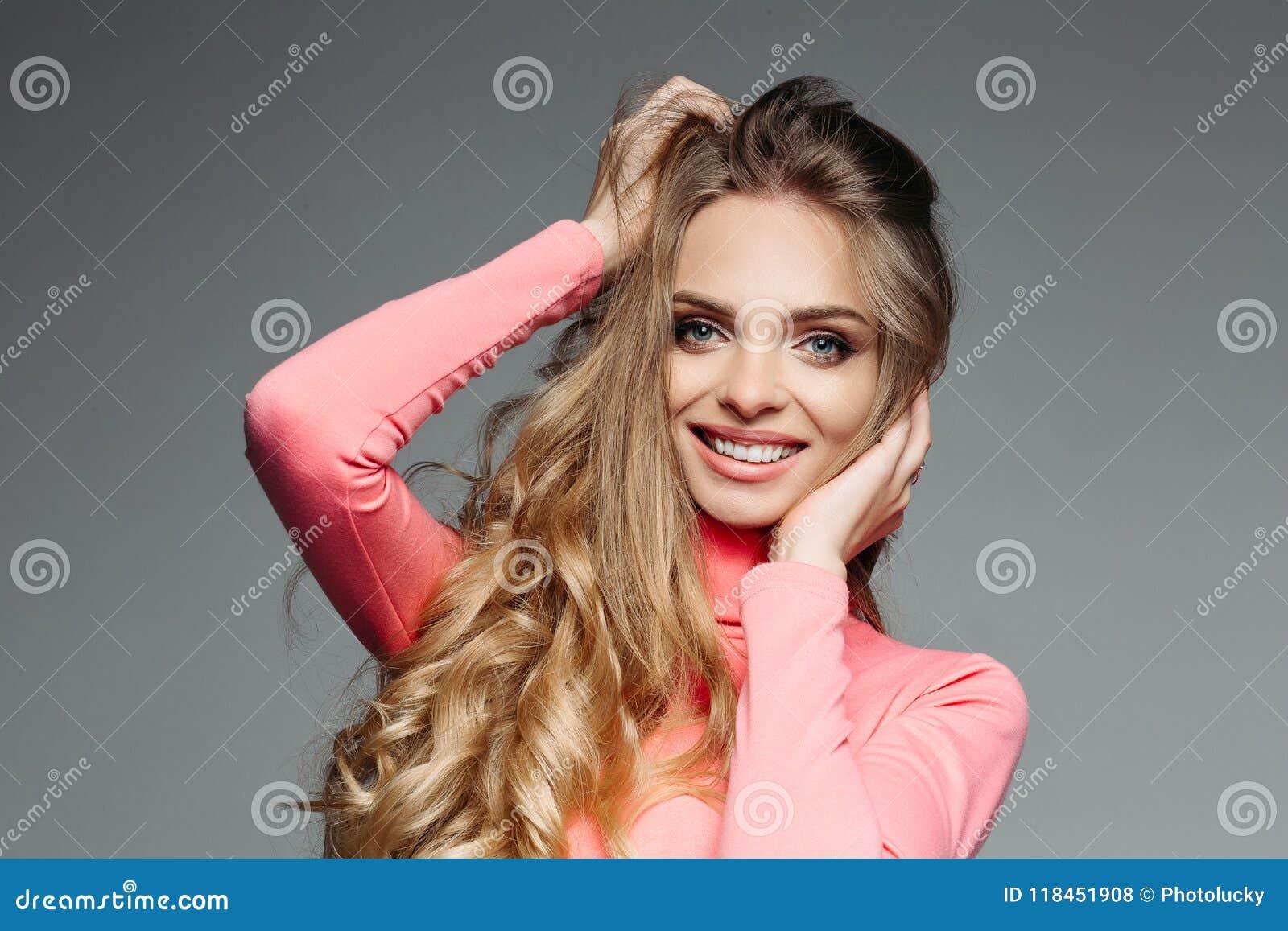 Pracowniany portret rozochocona piękna dziewczyna jest ubranym a z długim blondynka falistym, gęstym makijażem i