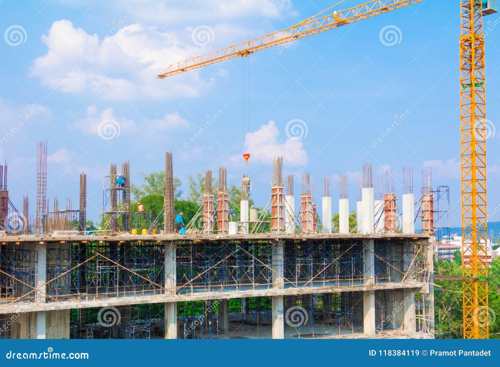 Pracownicy budowlani są usytuowanym przy laborer pracą plenerową która basztowego żurawia niebieskiego nieba tło z kopii sp i bud