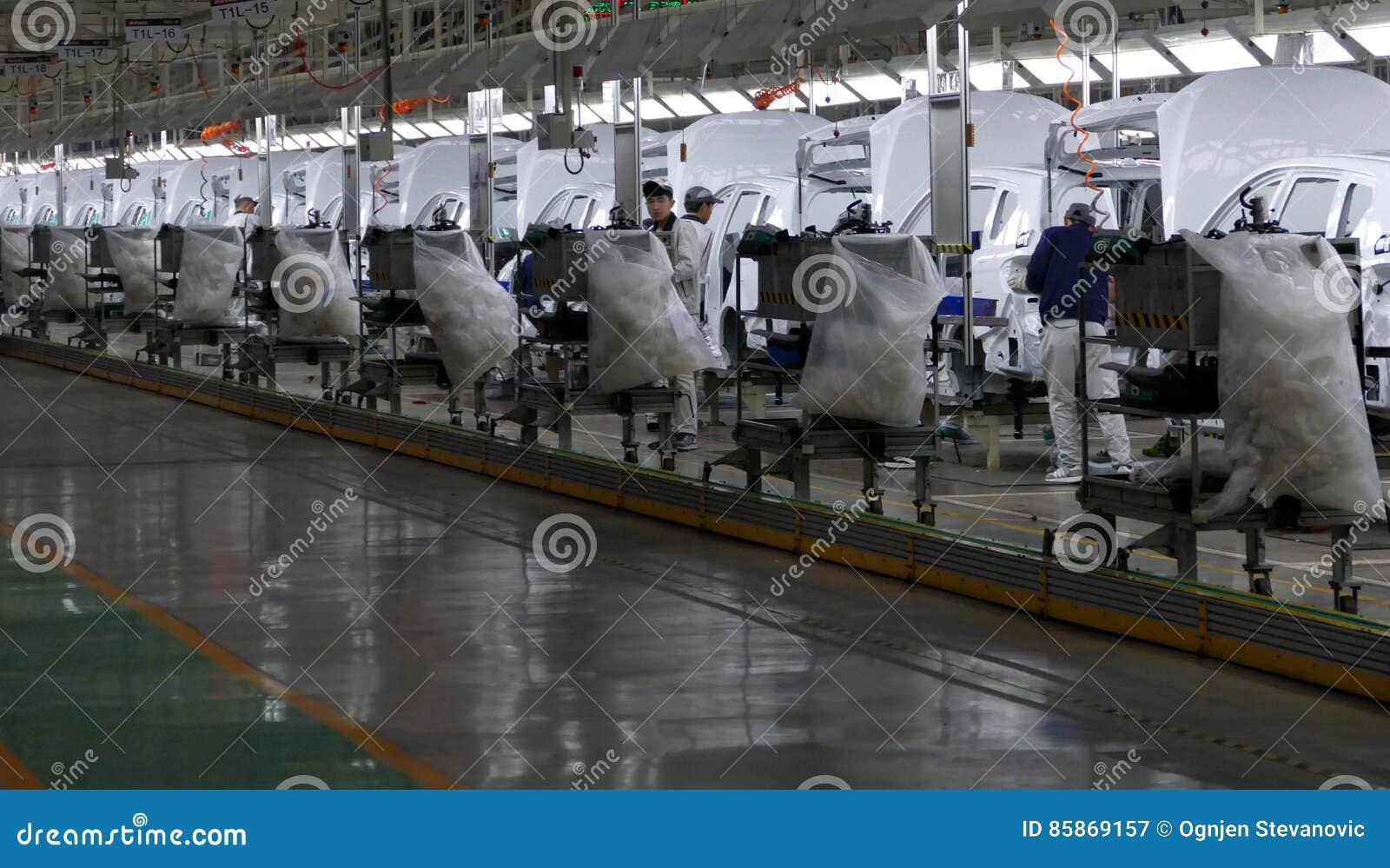 Pracownicy gromadzić samochód na linii montażowej w samochodowej fabryce