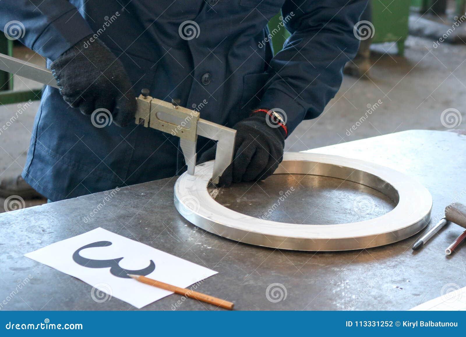 Pracownik inżynier mierzy część błyszczący metalu pierścionek flansza z caliper na pracującym żelazo stole w facto