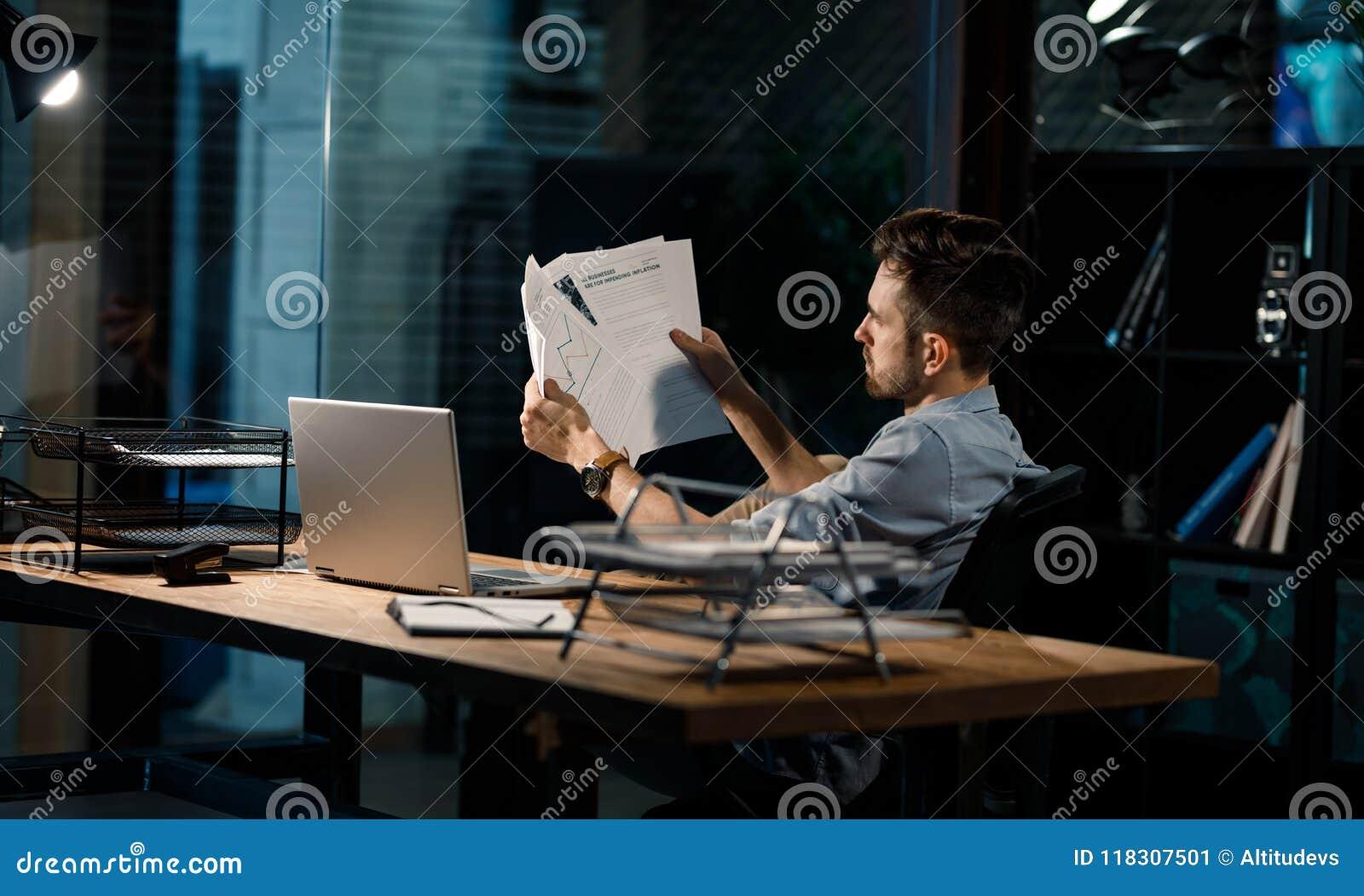 Pracownik patrzeje przez papierów