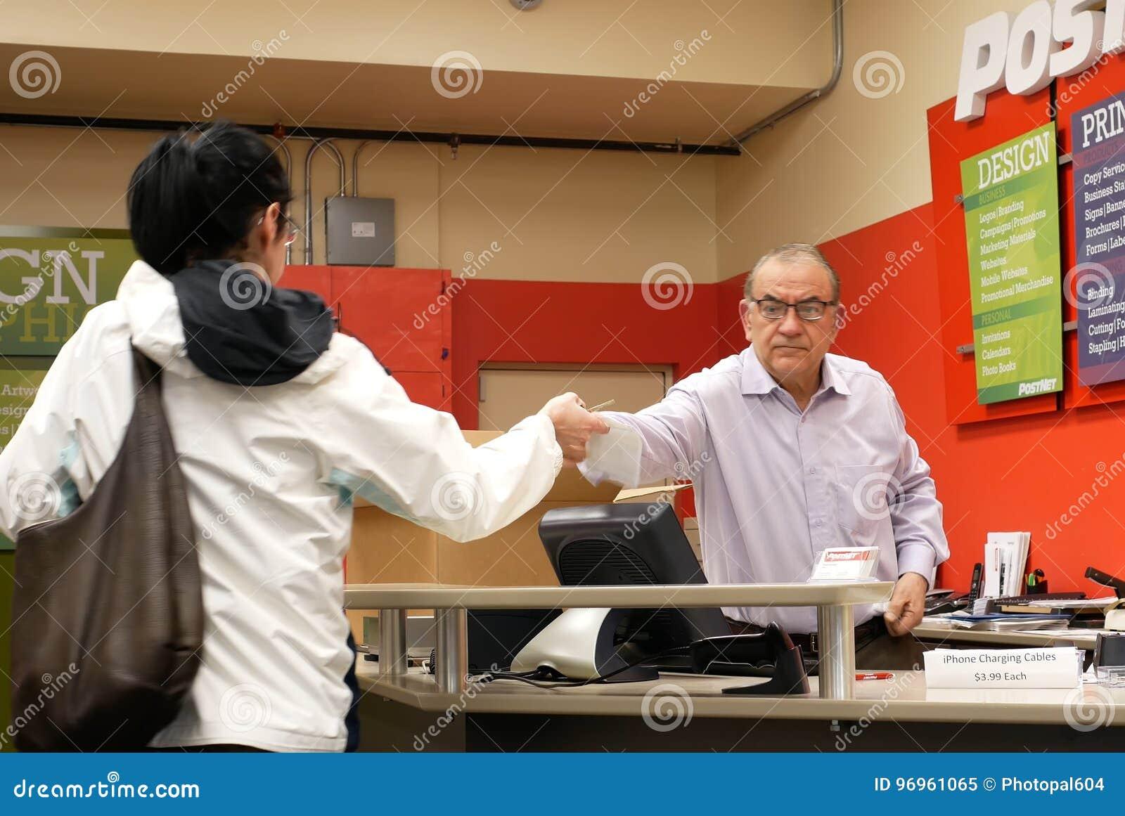 Pracownik sprawdza pakuneczek dla klienta przy urzędem pocztowym
