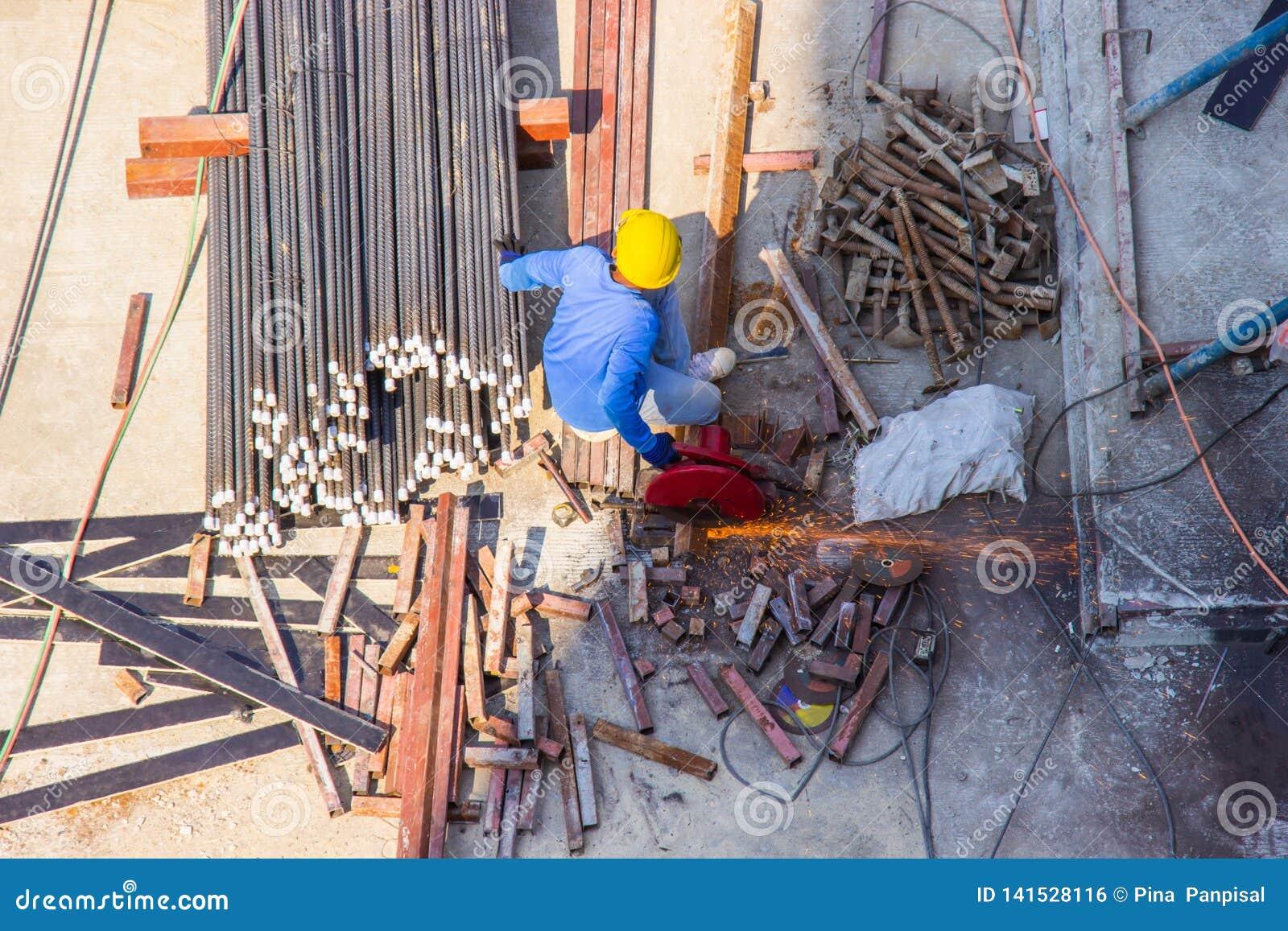 Pracownik używa elektryczną przemysłową stalową tnącej maszyny pracę w teren budowy budynku