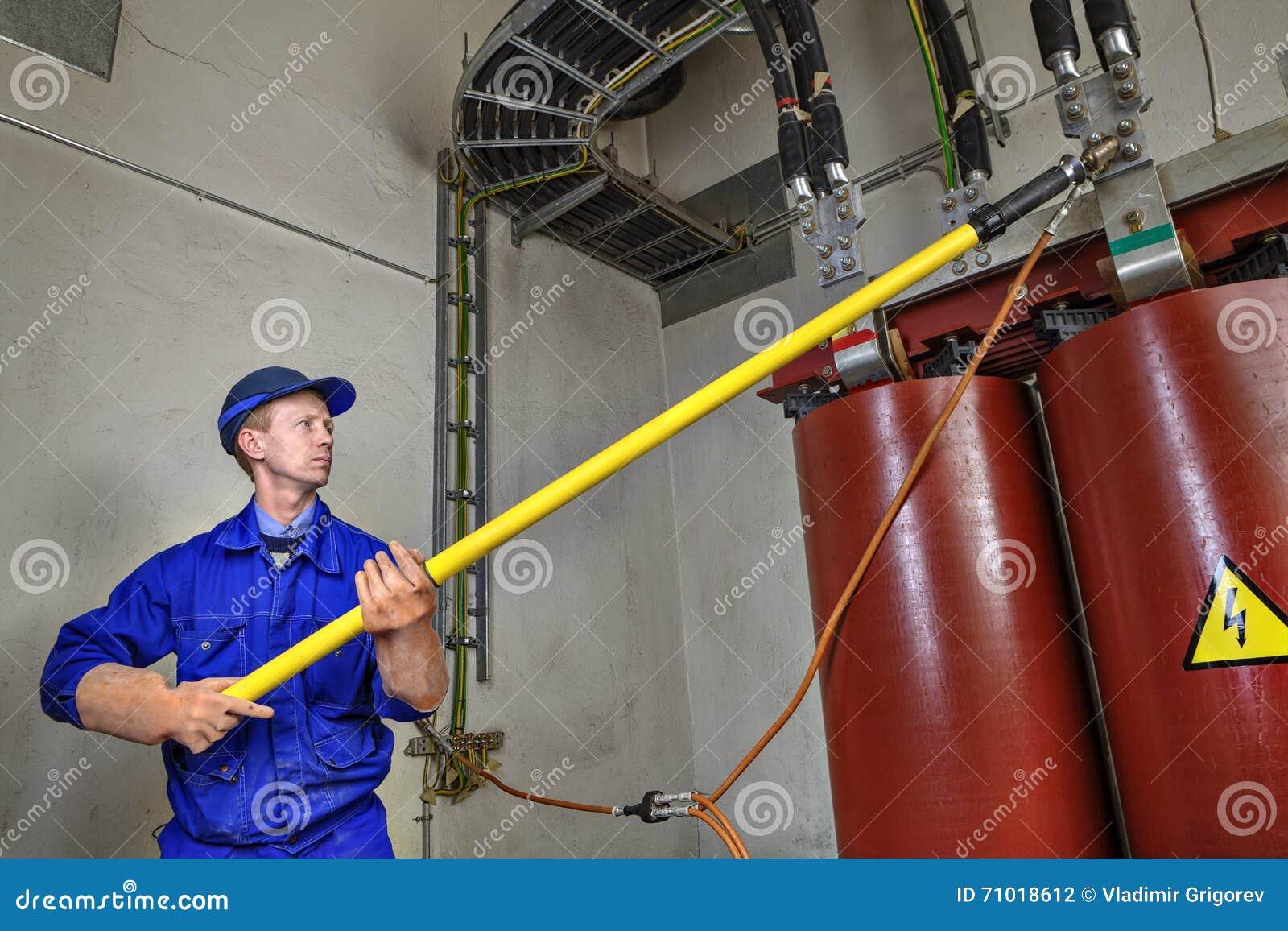 Pracownik używa izolowanie kij ziemski gruntowanie transformator