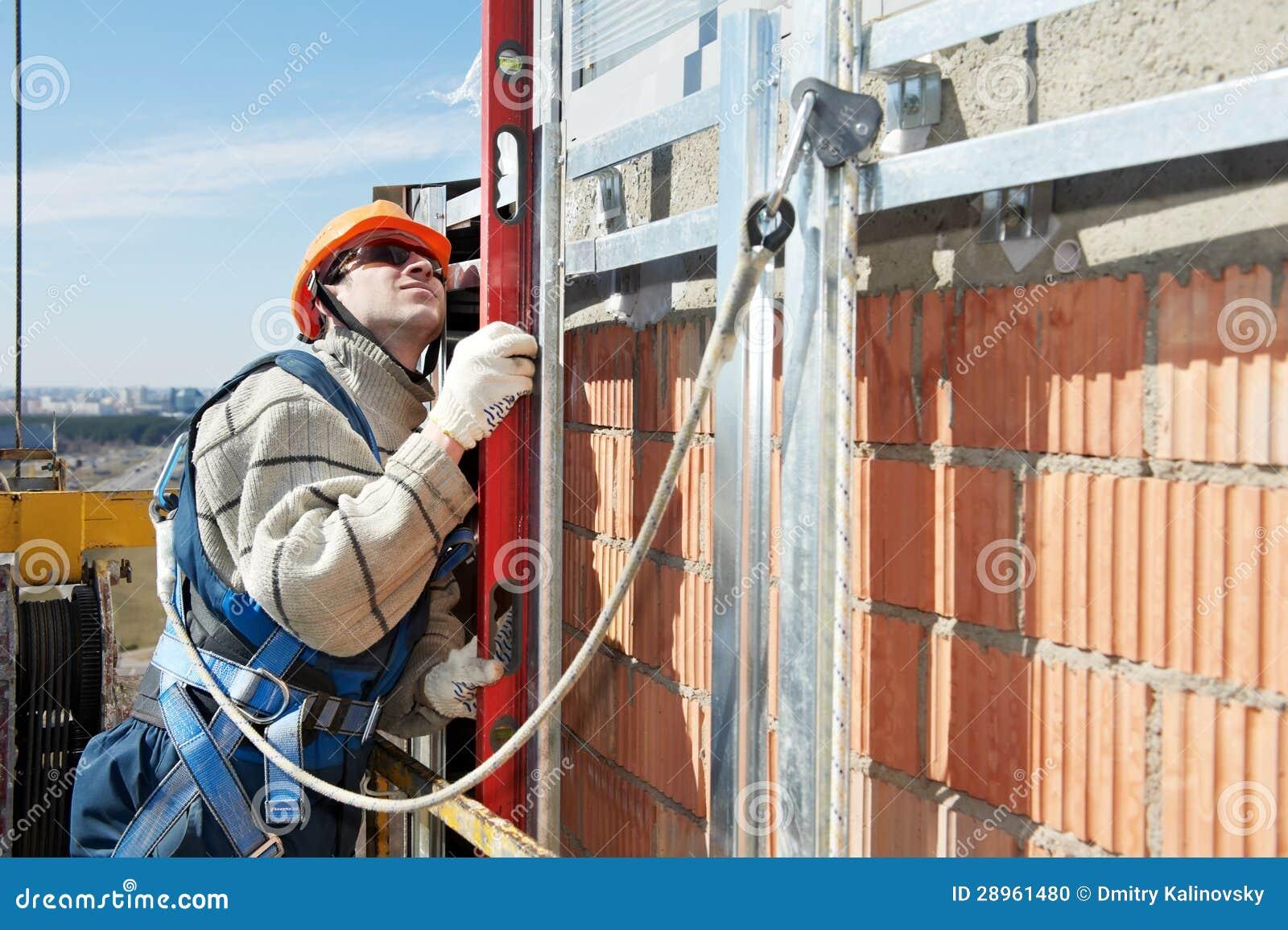 Pracownika budowniczy przy fasadowymi robotami budowlanymi