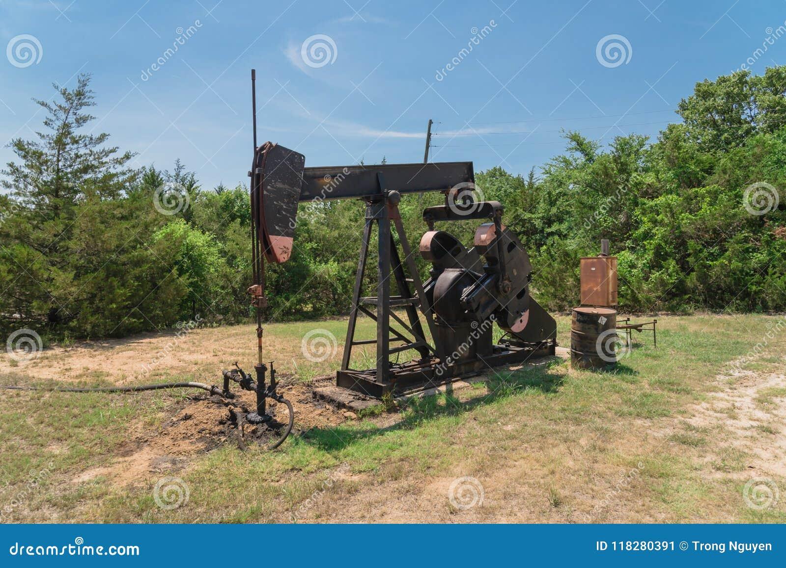 Pracująca pompowa dźwigarka pompuje ropę naftową przy odwiert naftowy miejscem w rurze