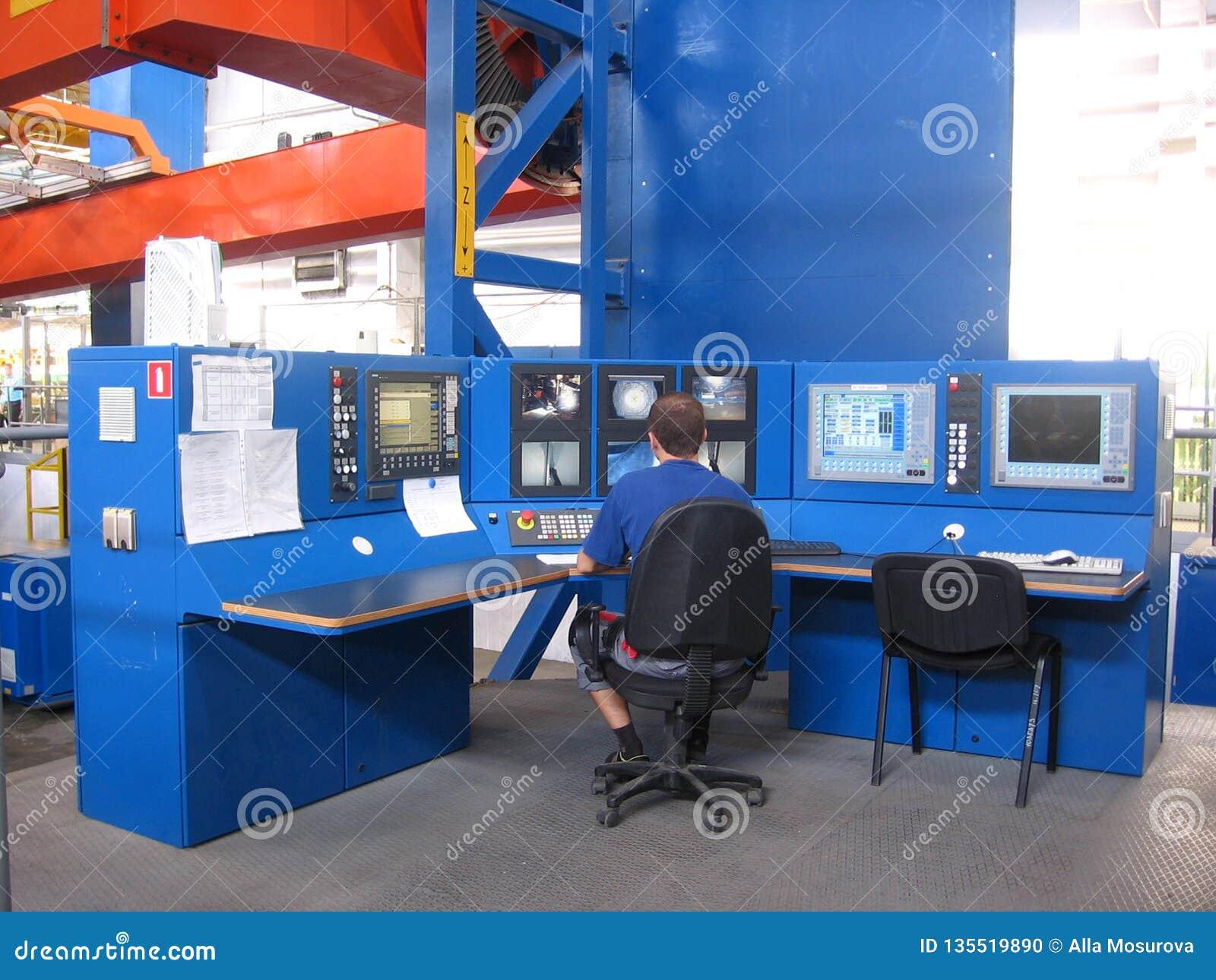 Pracującego specjalisty męski operator pracuje przy pulpit operatora przy rośliną w sklepie
