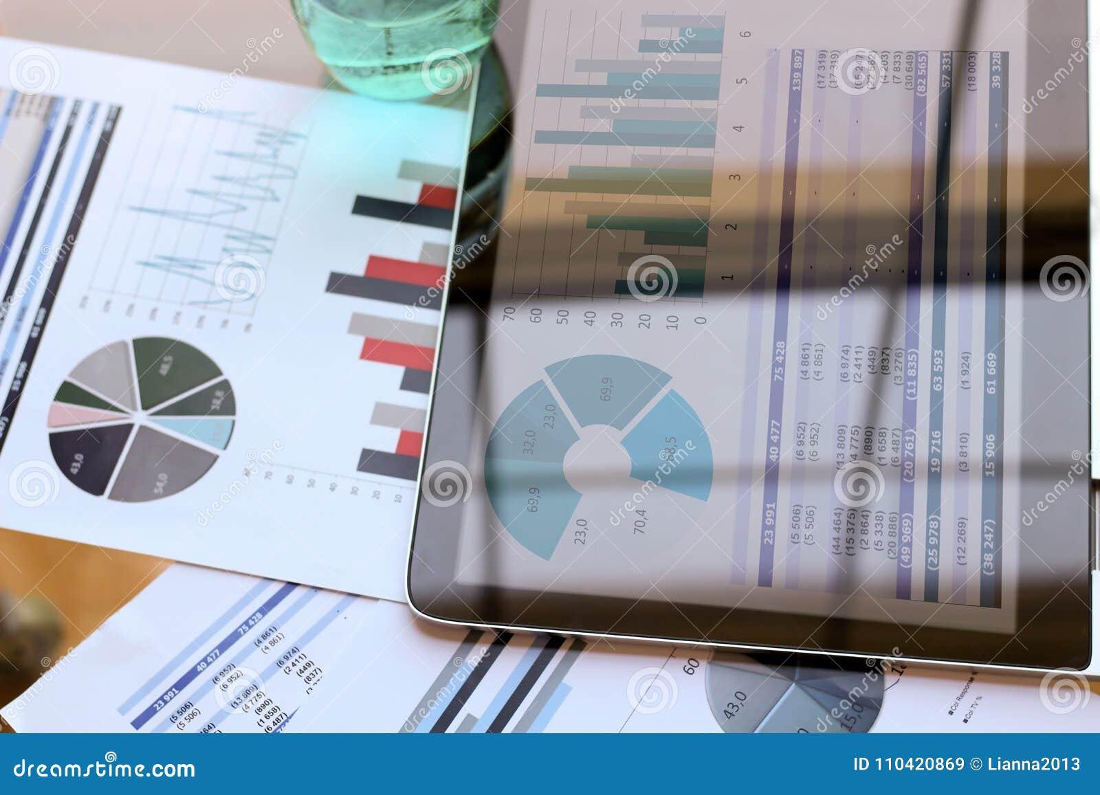 Pracujący miejsce z laptopem, cyfrowa pastylka; wykresy przy biurem