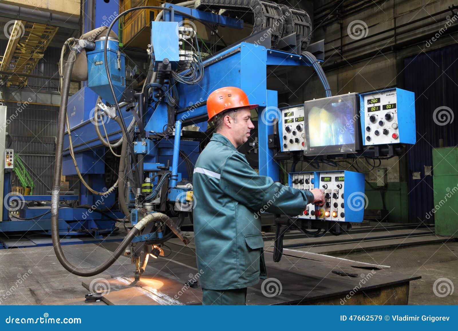 Pracujący operator kontrola spawalniczy robot, stoi przy kontrolną niecką