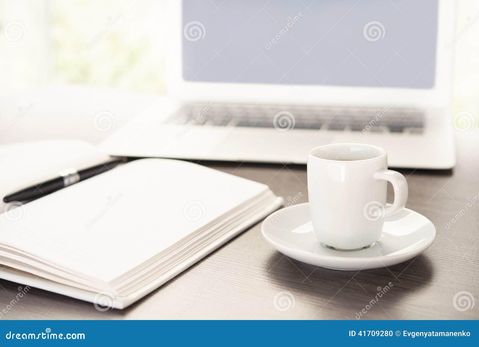 Pracuje biurko z filiżanka kawy komputerowym laptopem, notatnik, pióro