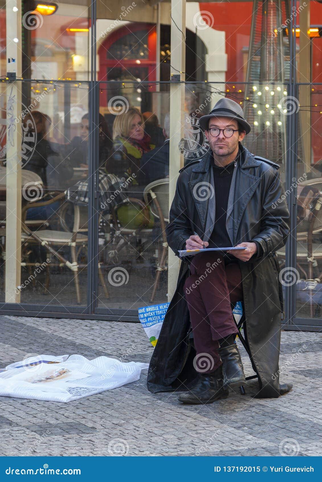 Praga, República Checa - 15 de marzo de 2017: un artista de sexo masculino dibuja un bosquejo mientras que se sienta en la calle