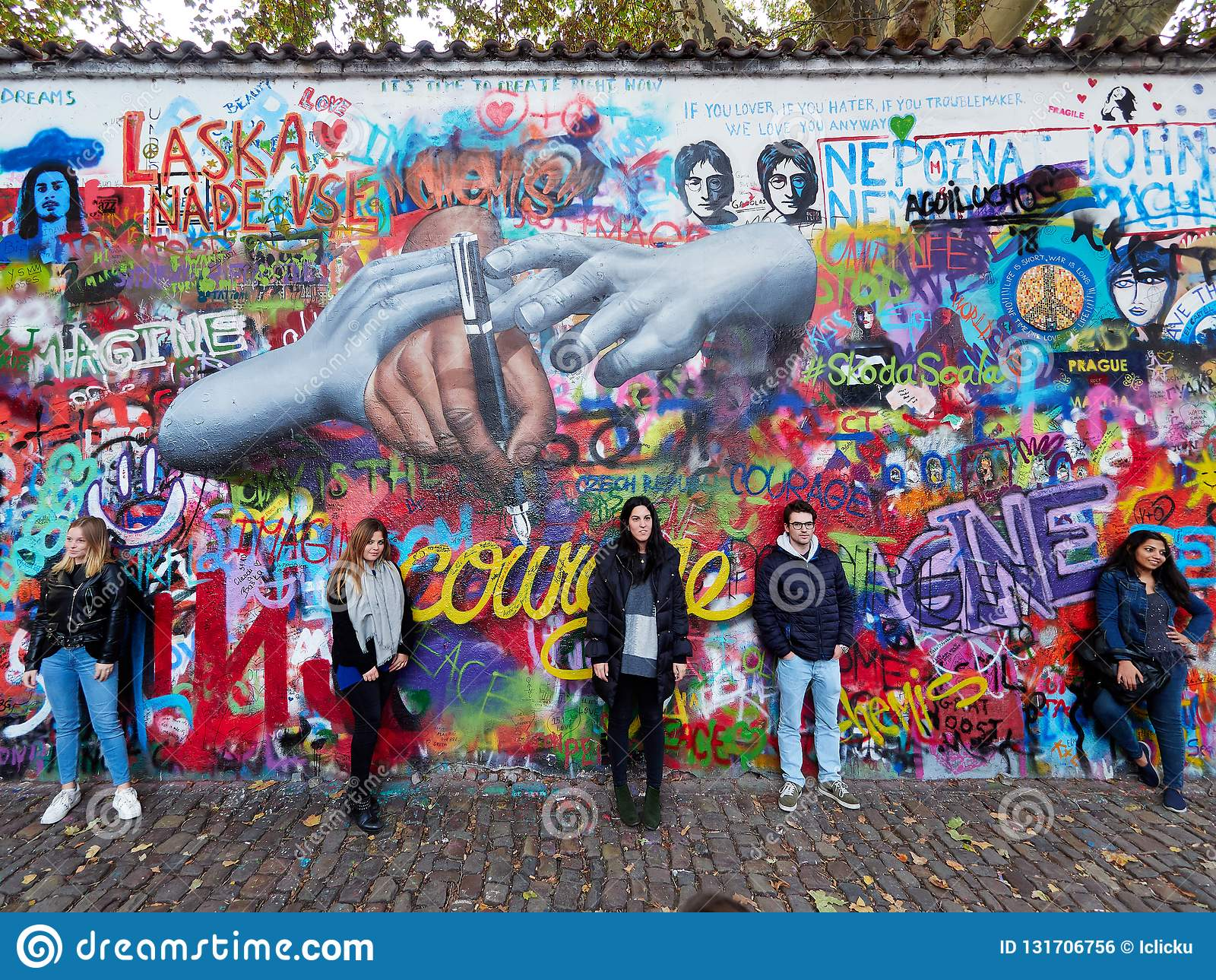 Praga, República Checa - 31 de outubro de 2018 os turistas levantam na frente da parede de John Lennon