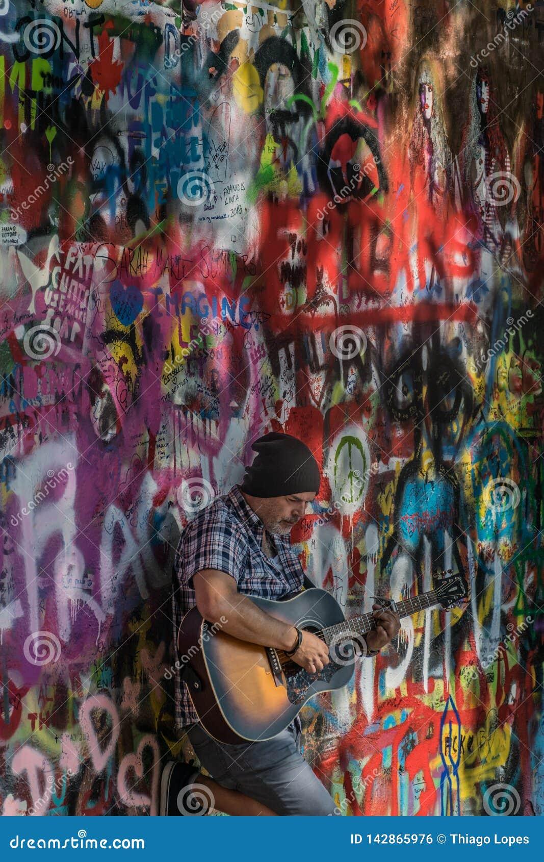 Praga, repubblica Ceca - 10 settembre 2019: Musicista ambulante della via che esegue le canzoni di Beatles davanti a John Lennon