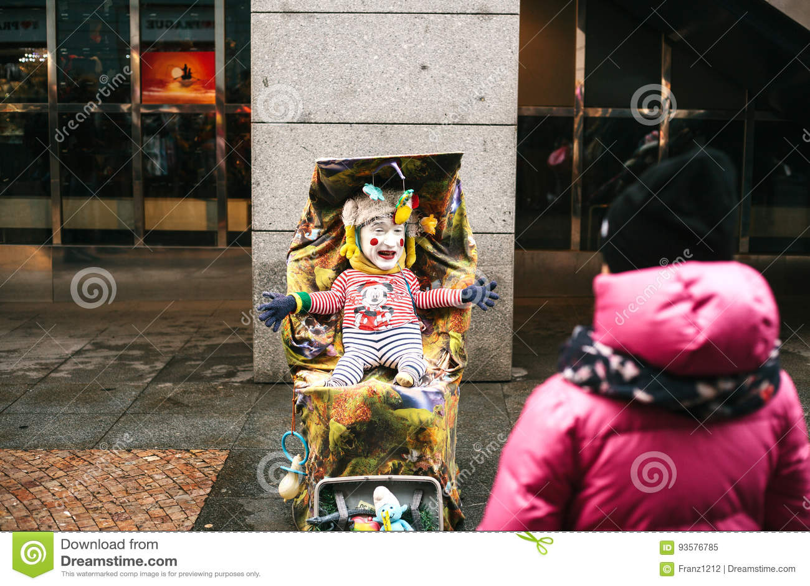 Praga, republika czech, Grudzień 24, 2016 - śmieszny błazen dorosły przebiera jako dziecko w spacerowiczu rozrywka