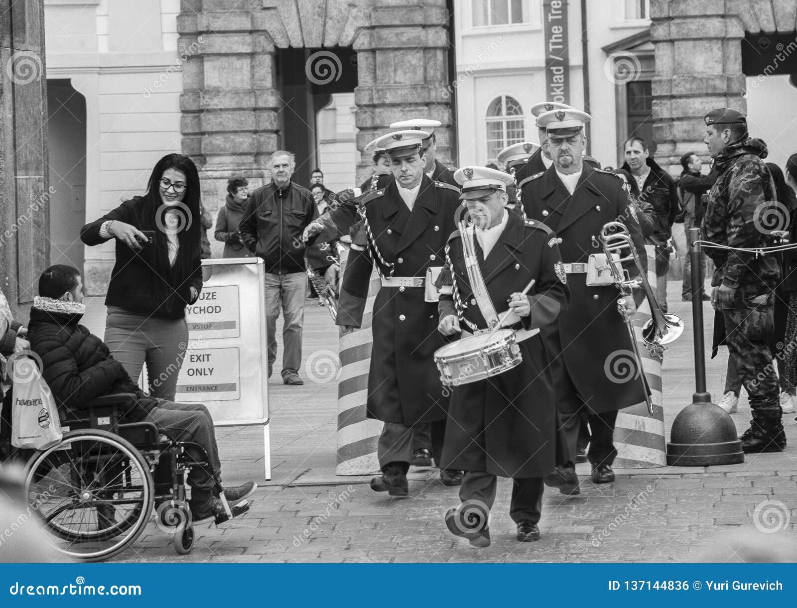 Praga, republika czech - Marzec 13, 2017: Militarni muzycy przechodzą turysty Czarny i biały wizerunkiem