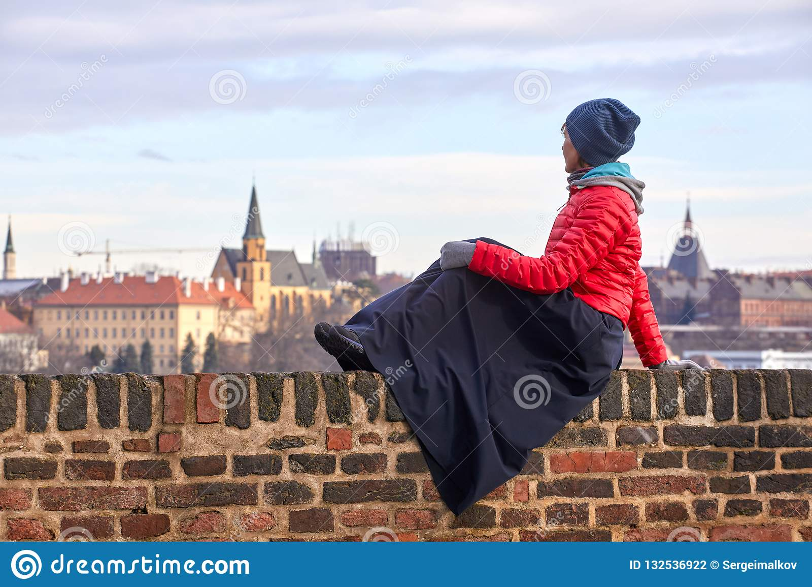 Praga Una mujer joven en una chaqueta roja se sienta en una pared de ladrillo y admira la vista de la parte histórica de la ciuda