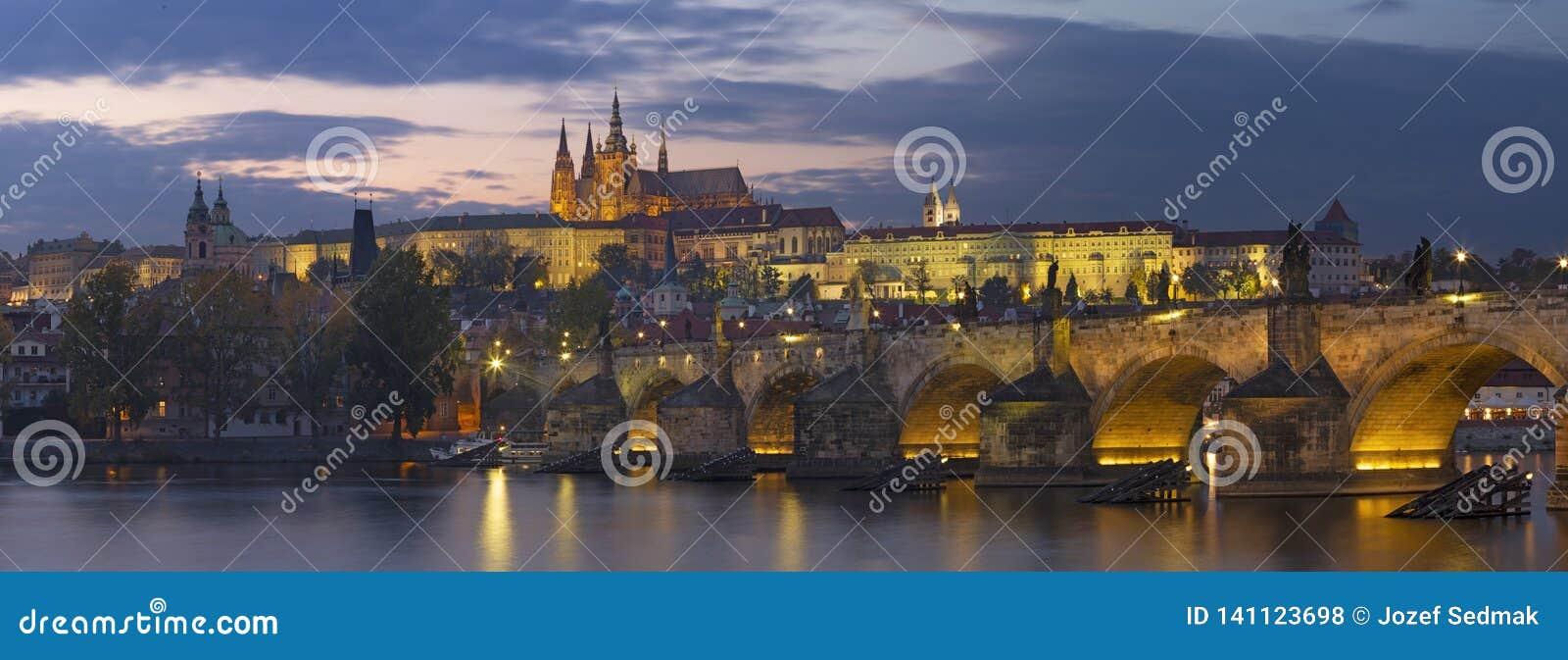 Prague - Charles Bridge, slotten och domkyrkan fr?n promenad ?ver den Vltava floden p? skymning