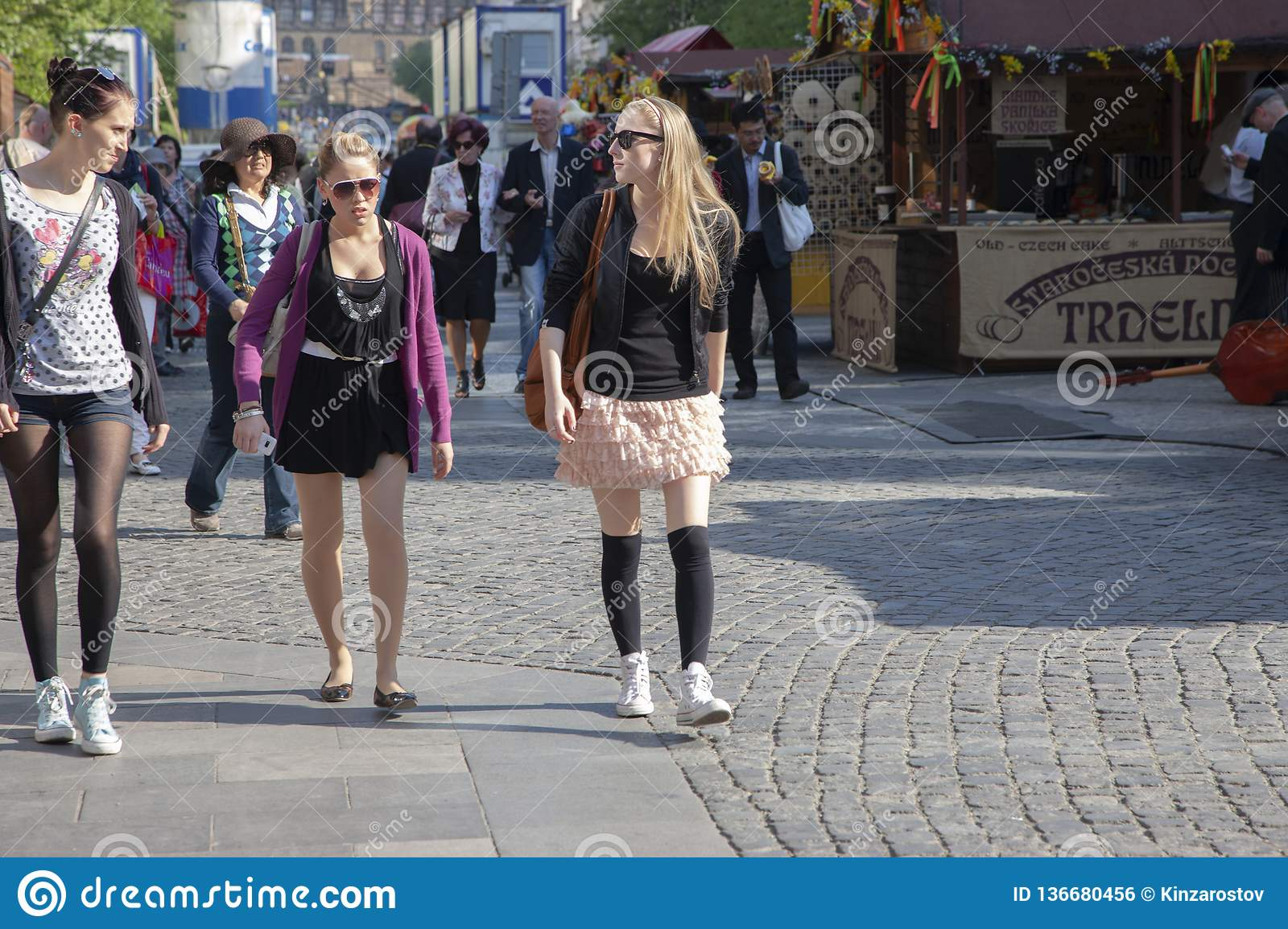 Prague, Czech Republic - April 20, 2011: Three young stylish women are smiling and walking down the street