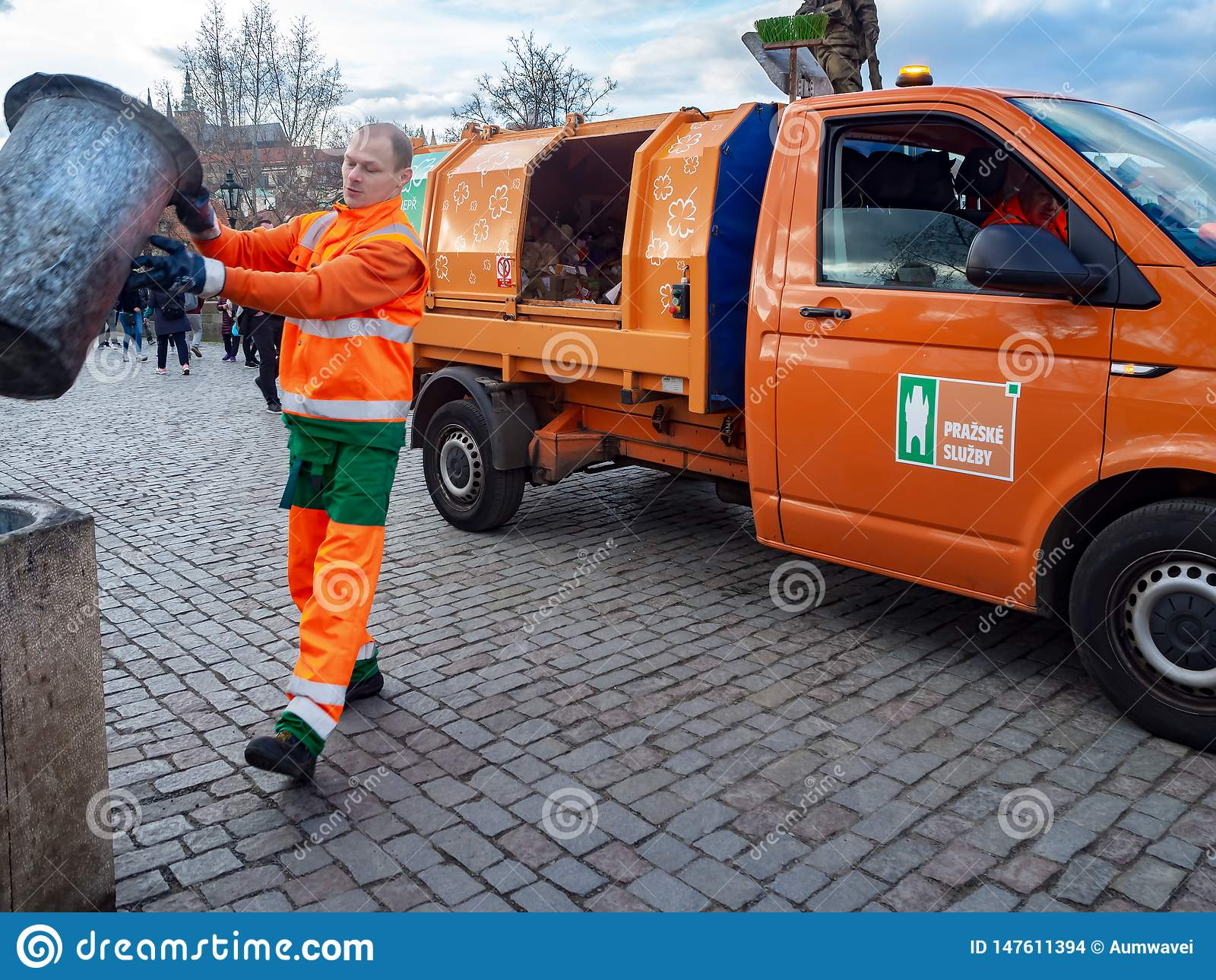 The garbage collector is pouring garbage into the garbage truck