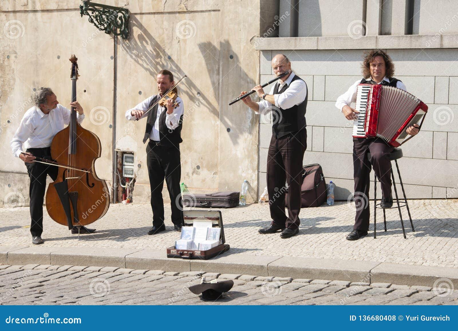 Prague Tjeckien - April 19, 2011: Kvartett av musiker som spelar musikinstrument för turister på gatan i Prague