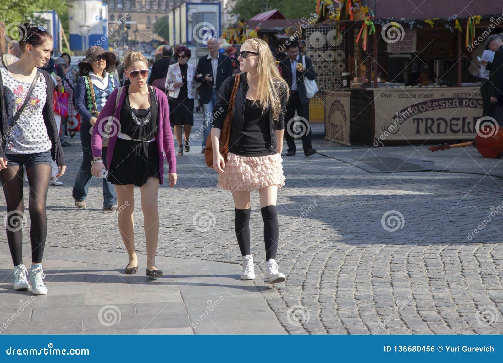 Prague Tjeckien - April 20, 2011: Tre unga stilfulla kvinnor är le och gå ner gatan
