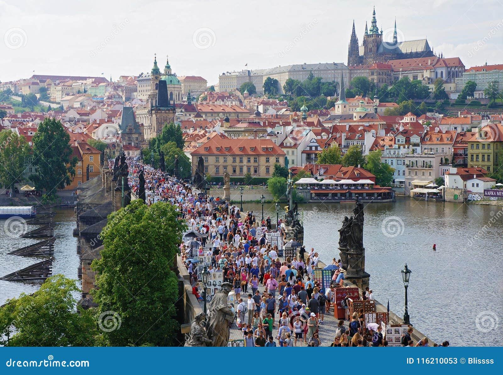 Prague Tjeckien - Augusti 14, 2016: Folkmassor av folk går på Charles Bridge - en populär turist- gränsmärke Prague townscape