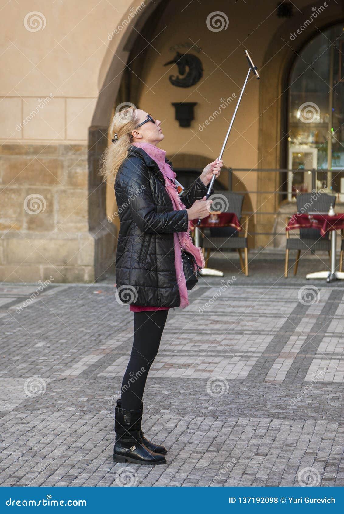 Prague Tjeckien - mars 15, 2017: Den gladlynta kvinnan med leendet som bär den moderna dräkten, gör selfie