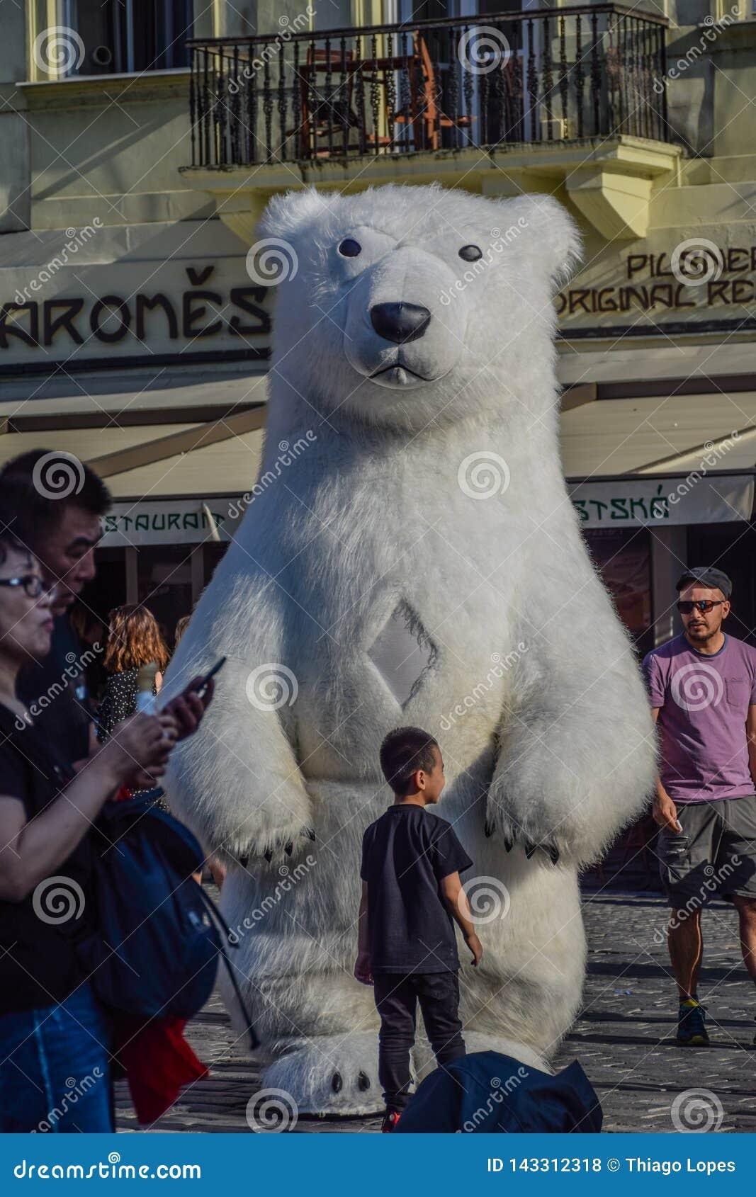 Prague Tjeckien - September, 17, 2019: Roliga ungar spelar med en jätte- uppblåsbar isbjörn i den gamla staden
