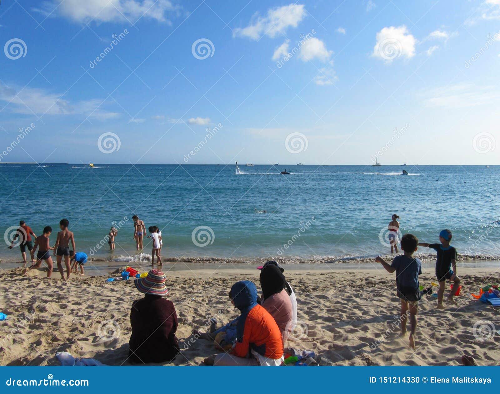Praia bonita As mulheres muçulmanas estão descansando na areia na roupa e nos chapéus