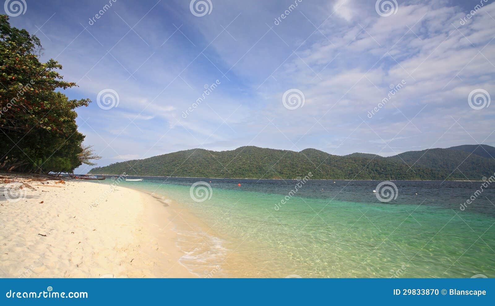 Praia branca da areia contra o mar de cristal no Koh Rawi
