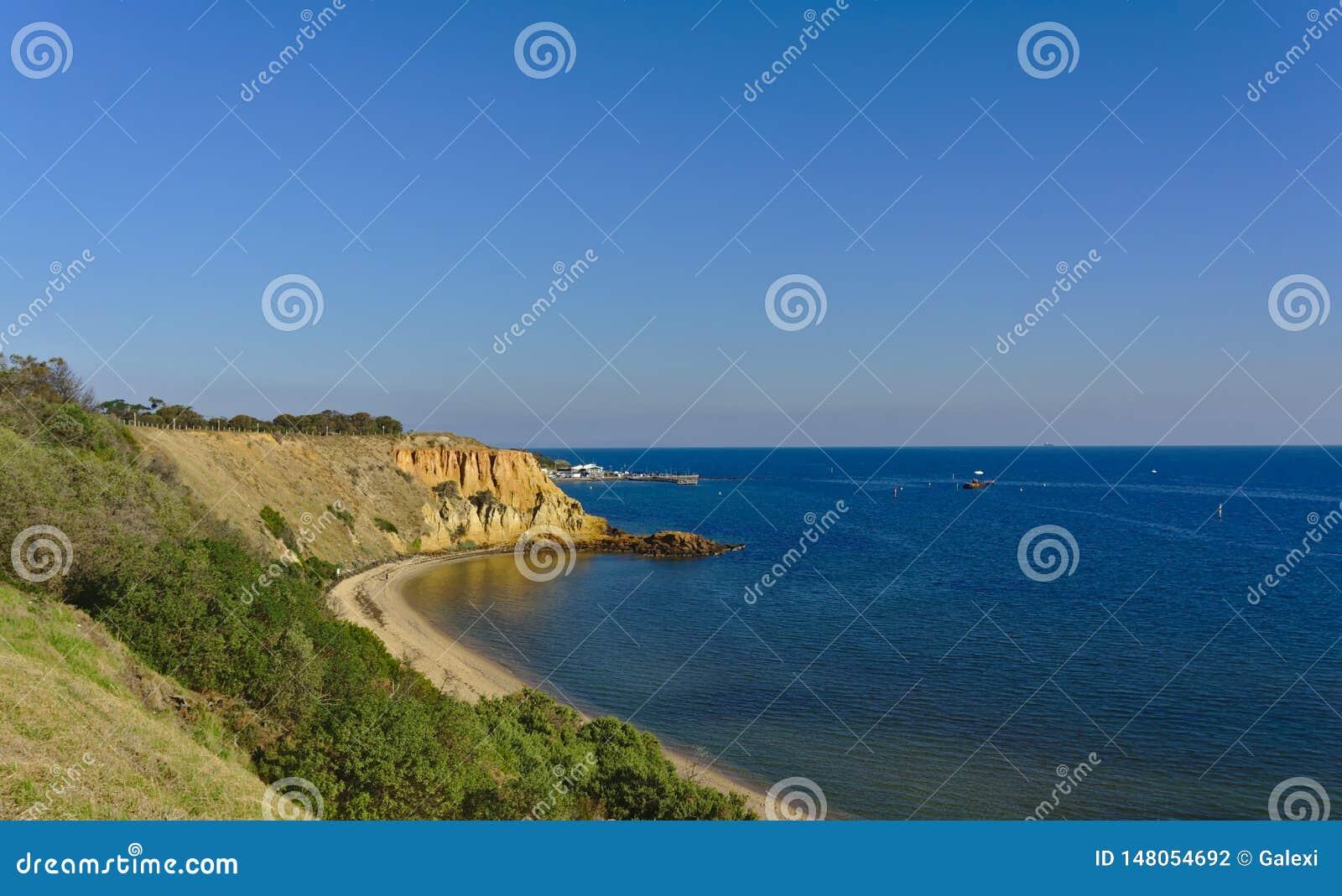 Praia com os penhascos no dia ensolarado