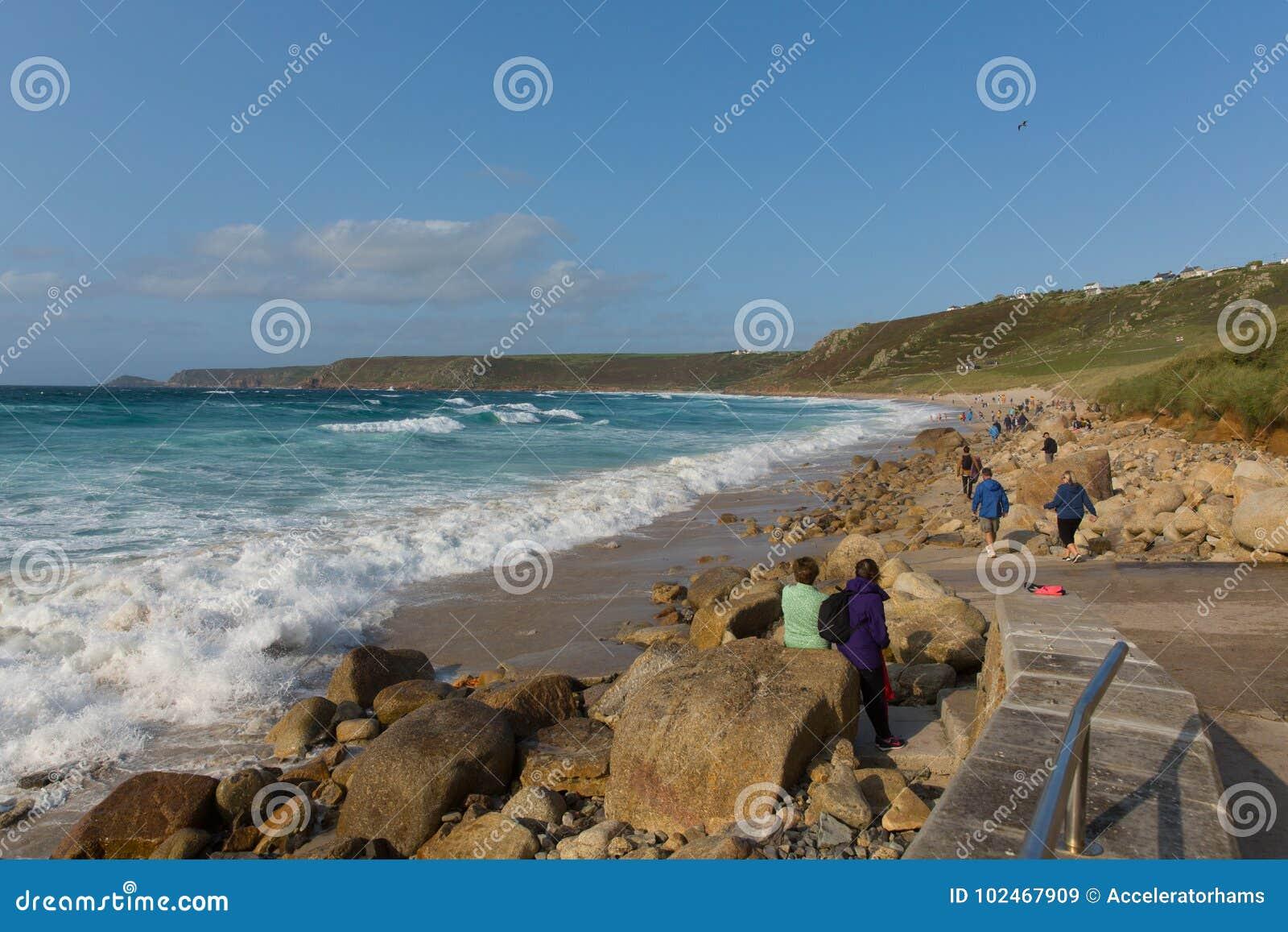 Praia Cornualha da angra de Sennon com os povos que apreciam as ondas azuis do mar e do branco
