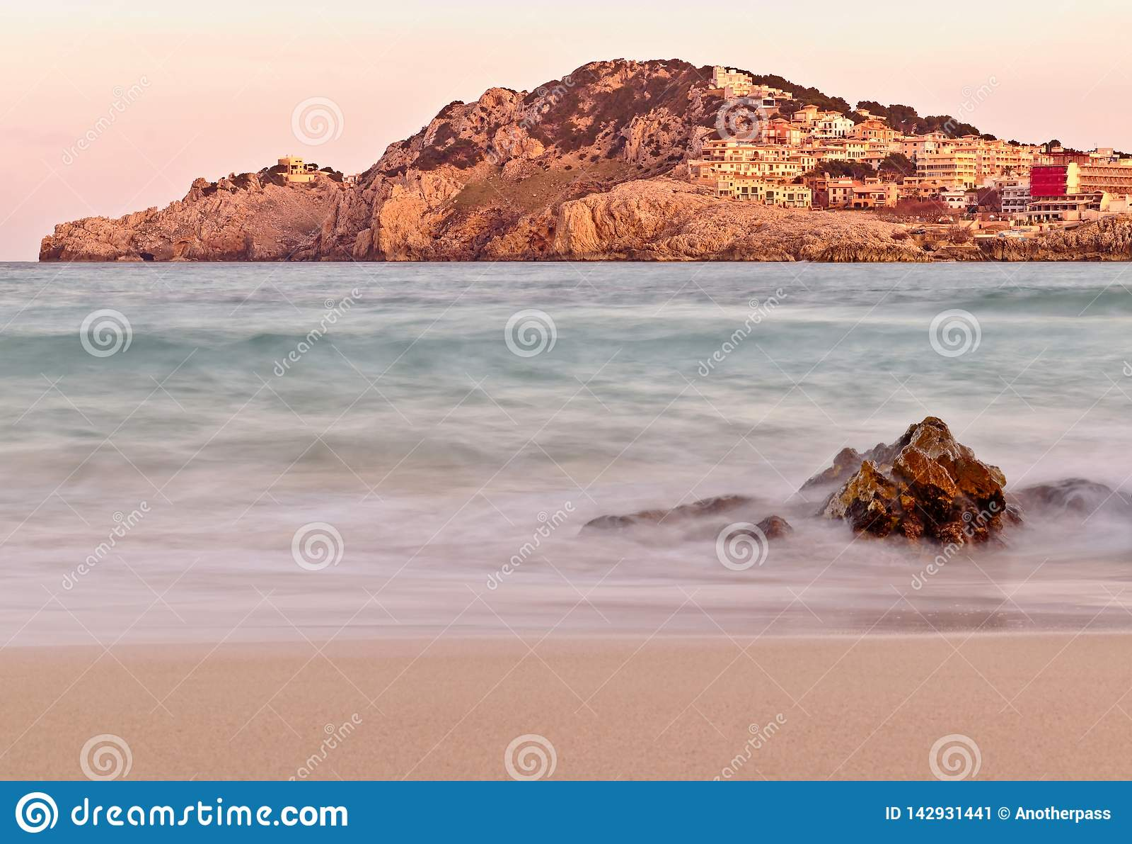 Praia de Cala Agulla no por do sol, com monte e cidade mais o primeiro plano rochoso, mallorca, spain