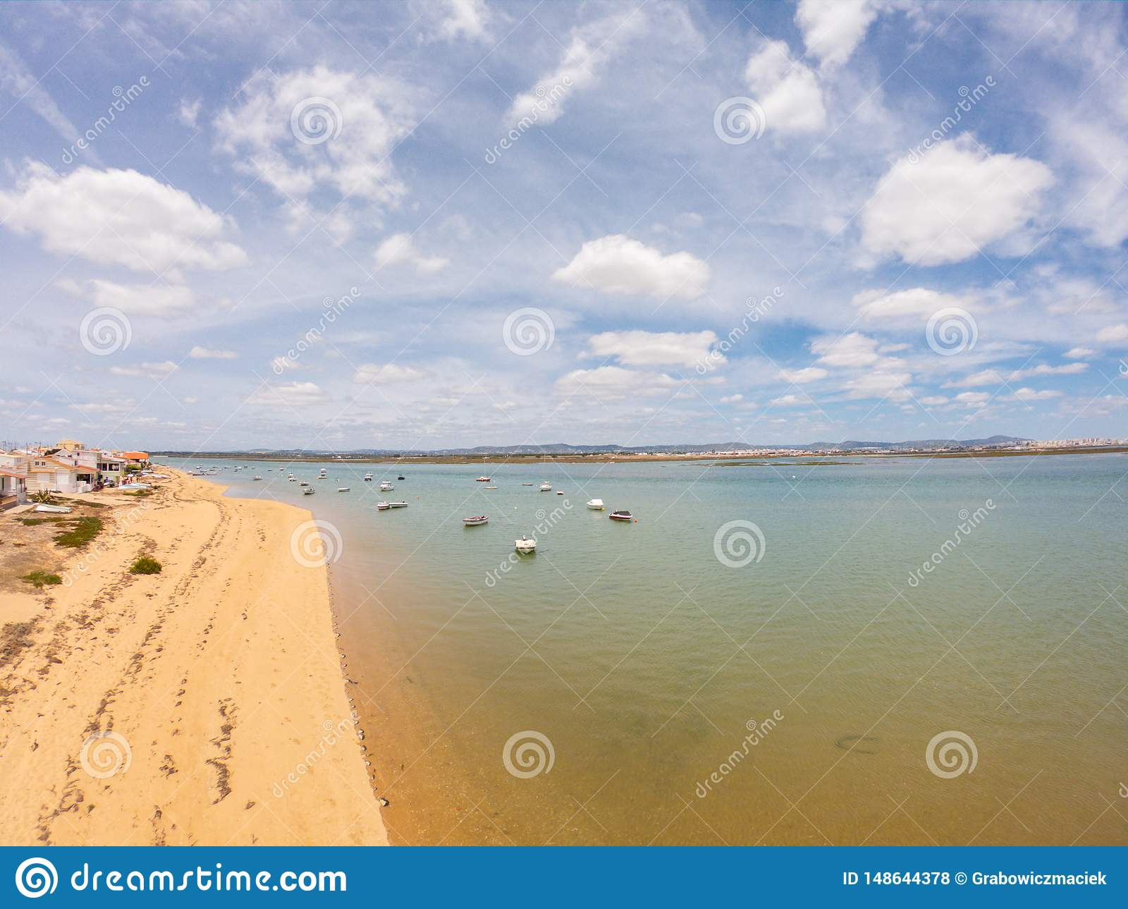 Praia De Faro, Algarve, Portugal. Aerial view on coast of ocean and beach. Boats on water, drone view