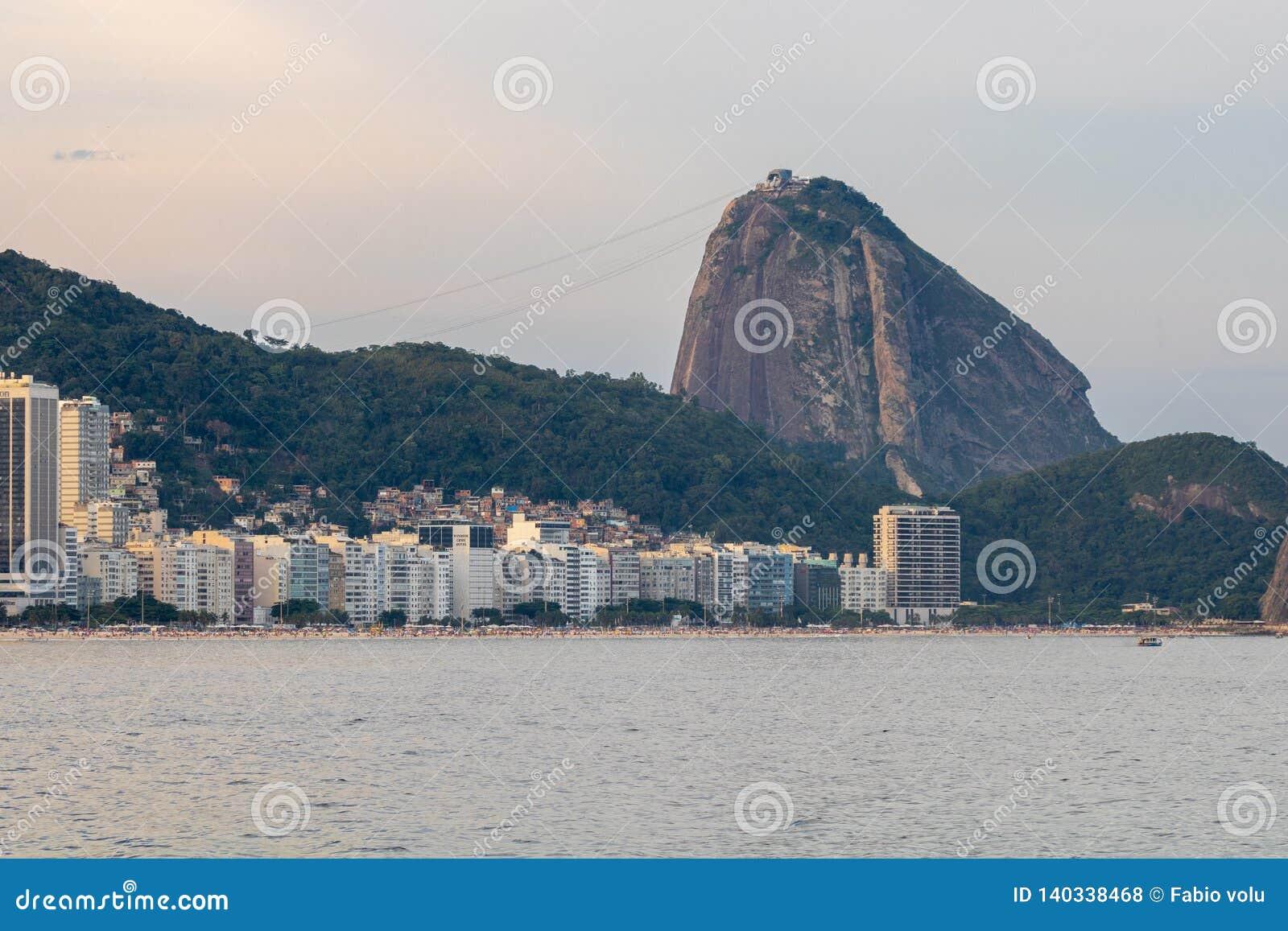 Praia de Leme e de Copacabana em Rio de janeiro que negligencia o naco de açúcar no por do sol