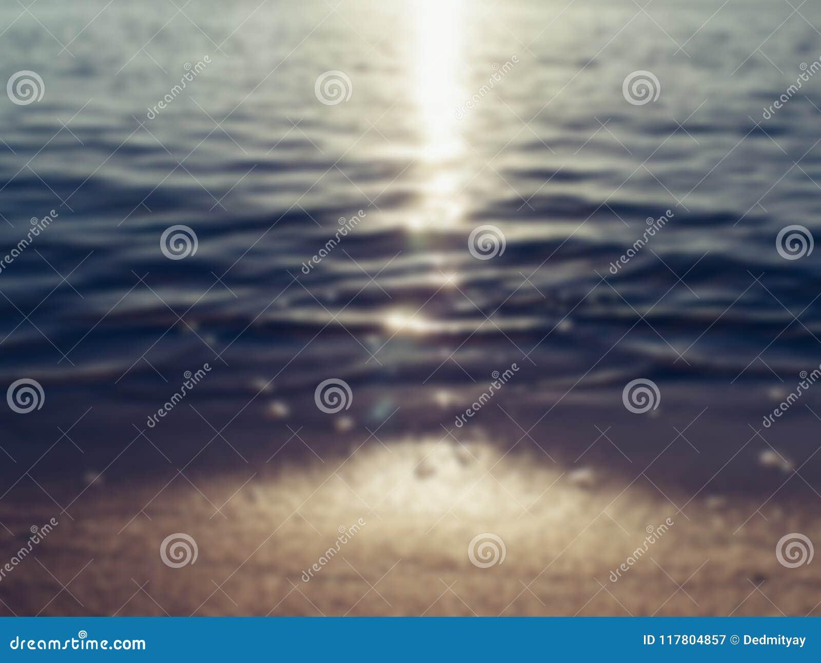 A praia e o mar da areia acenam na luz do por do sol, fundo abstrato borrado do verão