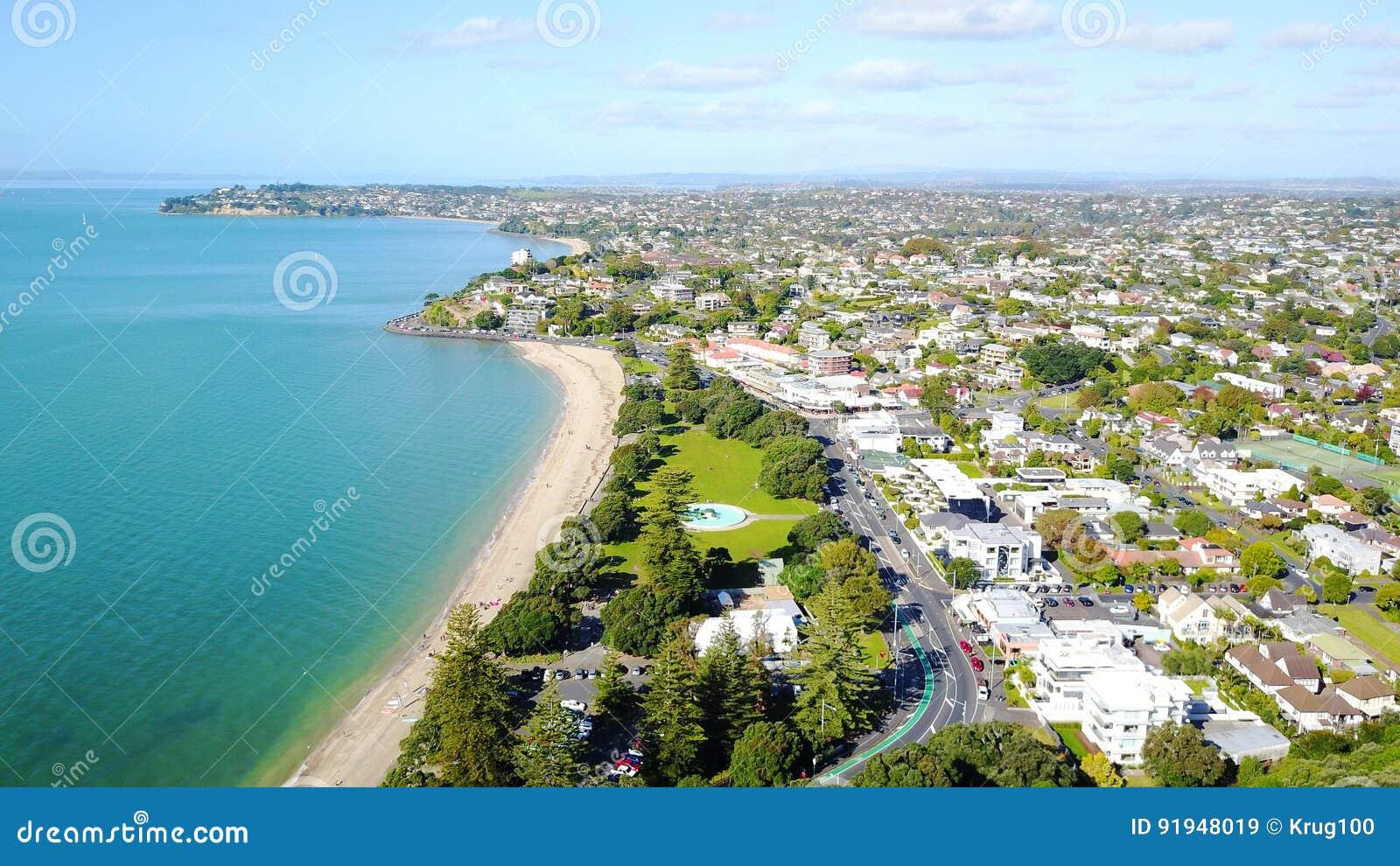 Praia ensolarada com subúrbio residencial no fundo Auckland, Nova Zelândia